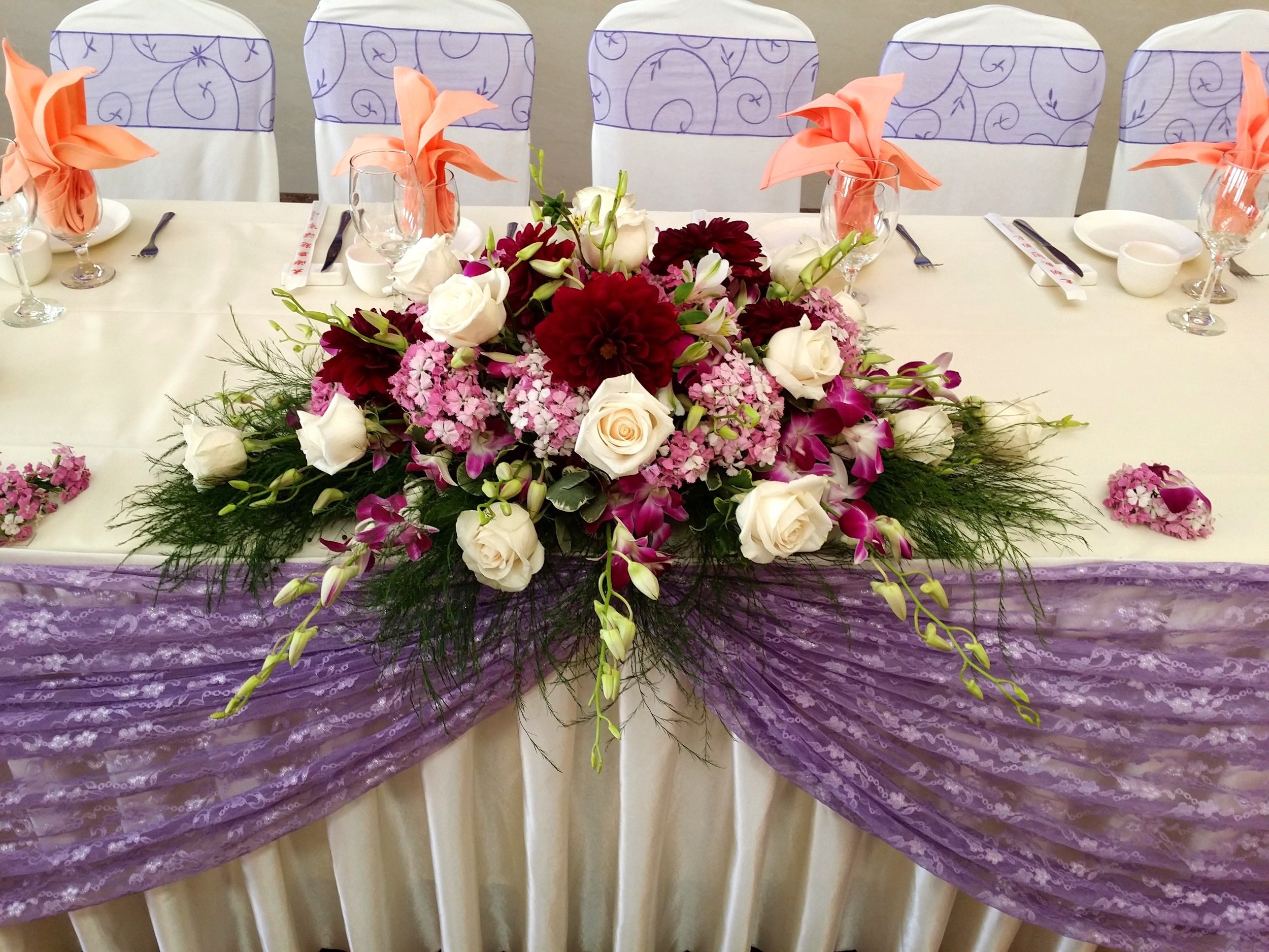 - This is another head table centerpiece that highlights different flowers. What makes this one stand out is the stark contrast of the light and dark that these different flowers bring.