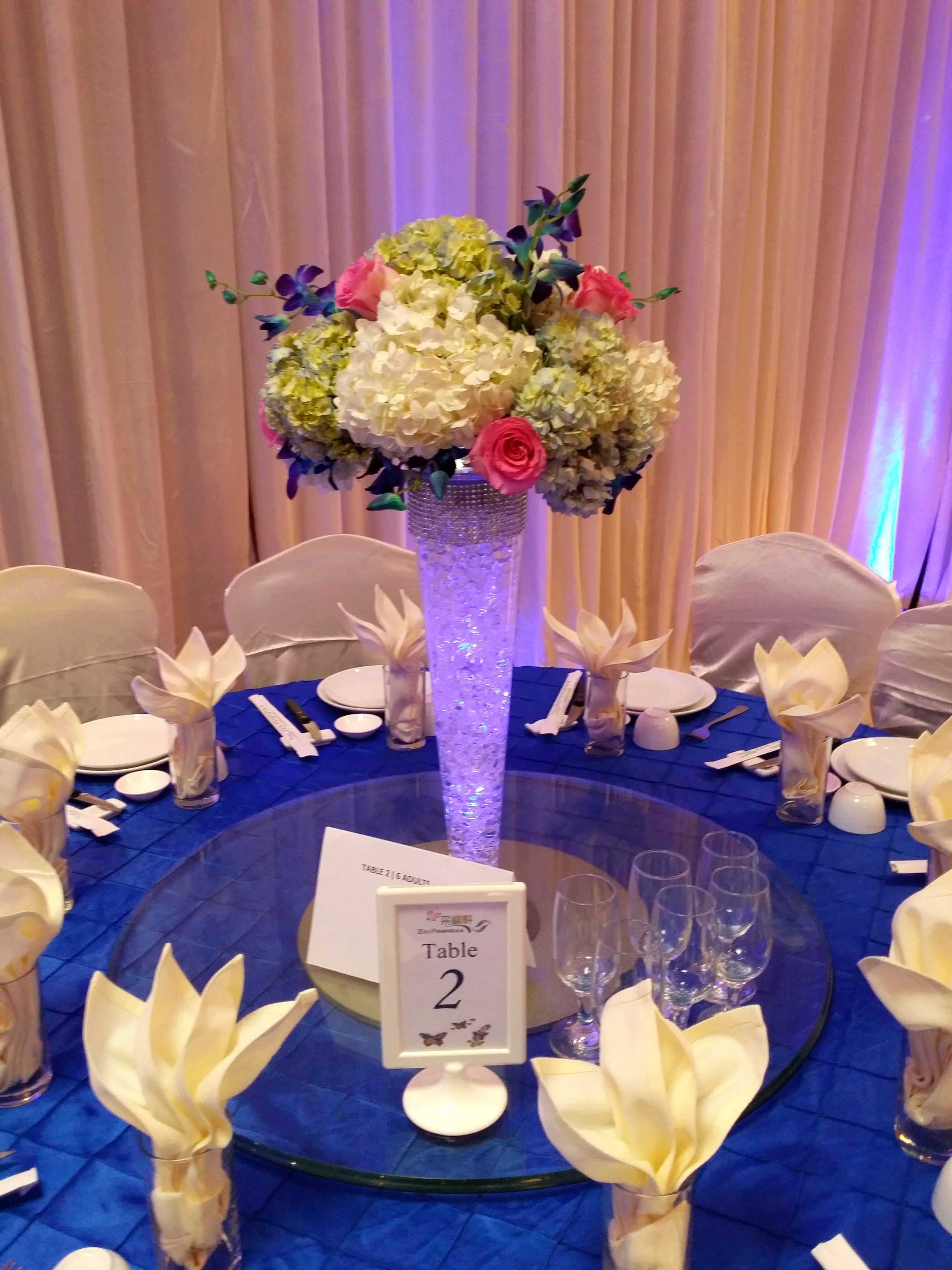 - We love creating an interesting guest table centerpiece, and the blue tablecloths allowed us to create a wedding centerpiece with height to stand out and make a statement.