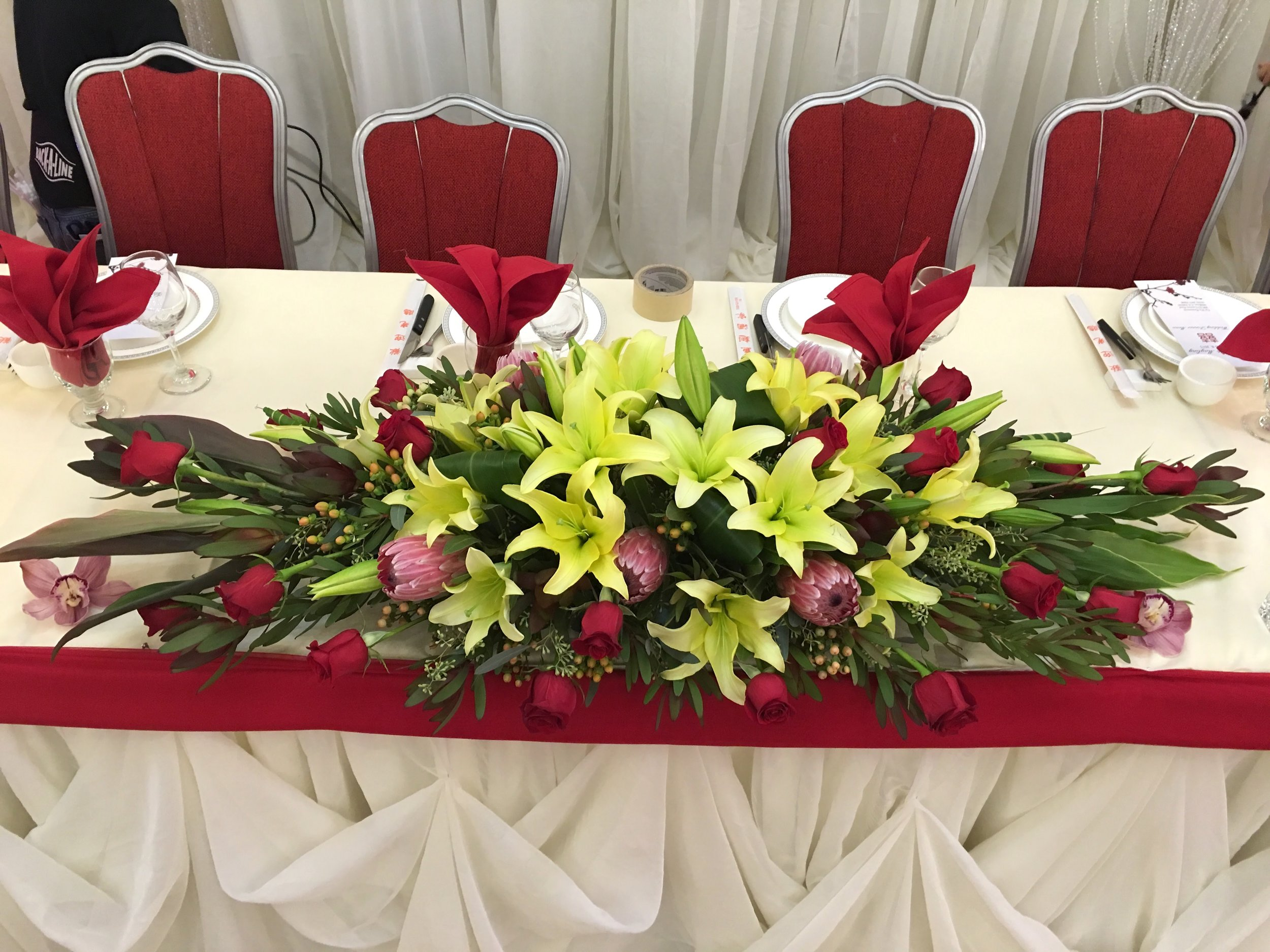 - We wanted to create a focal point in this wedding centerpiece using lilies to draw attention. With the brightest colors in the middle, this centerpiece leads your eyes straight to the bride and groom.