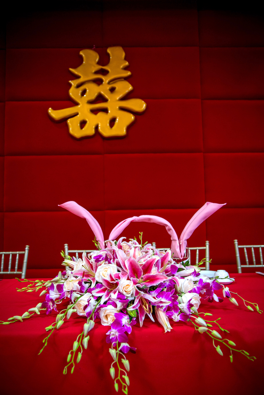 - Orchids are some of the most beautiful flowers, with their long stems and multiple blooms. This wedding centerpiece focuses on the bride and groom, with the orchid blooms cascading down and making the centerpiece look bigger.