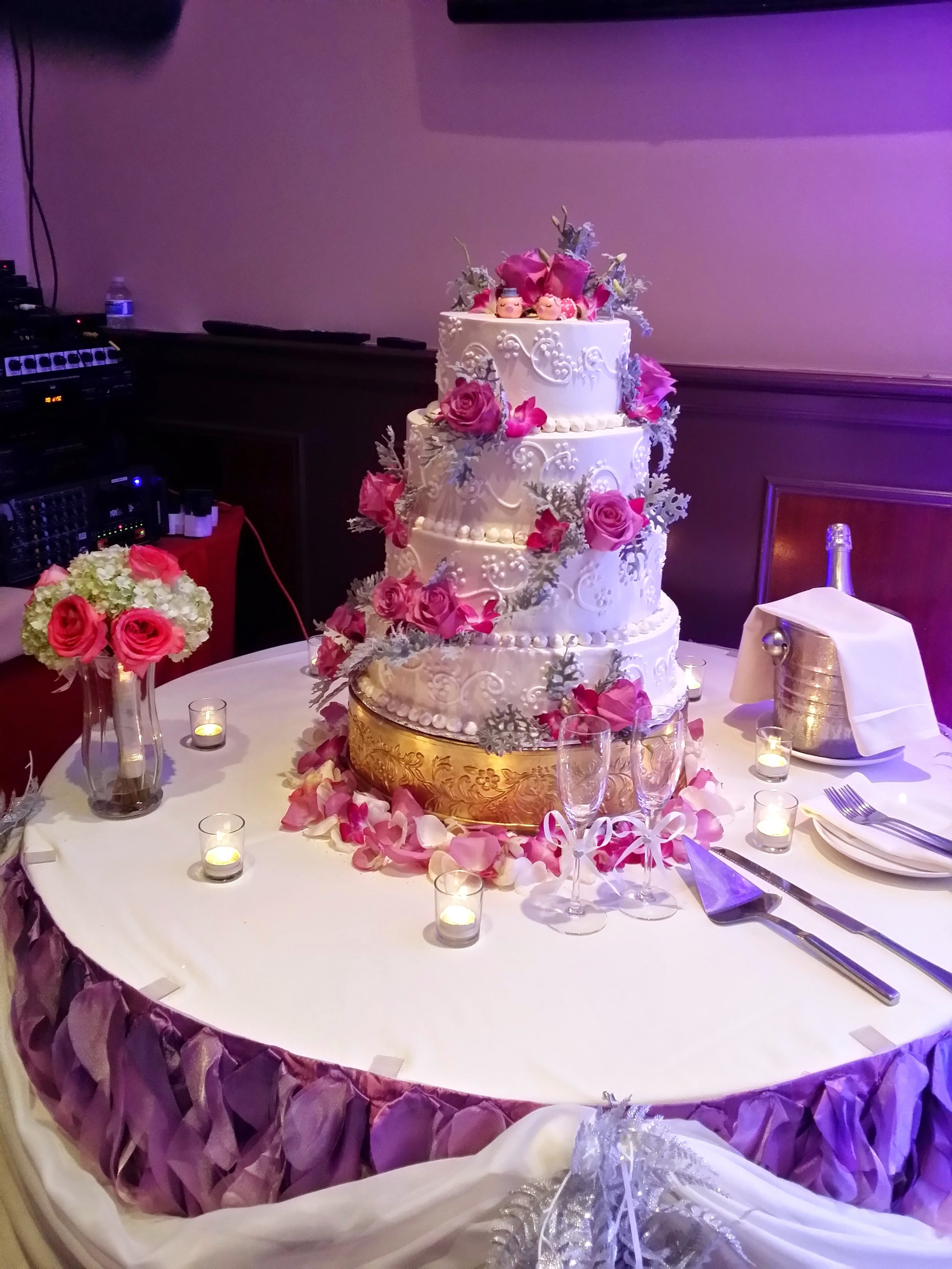 - This lovely 4-tiered cake had such intricate piping that we wanted to make sure we didn't take away from it. We also knew that there needed to be a pop of color to draw the attention of wedding guests, so we scattered roses and dusty miller sparsely around the wedding cake.