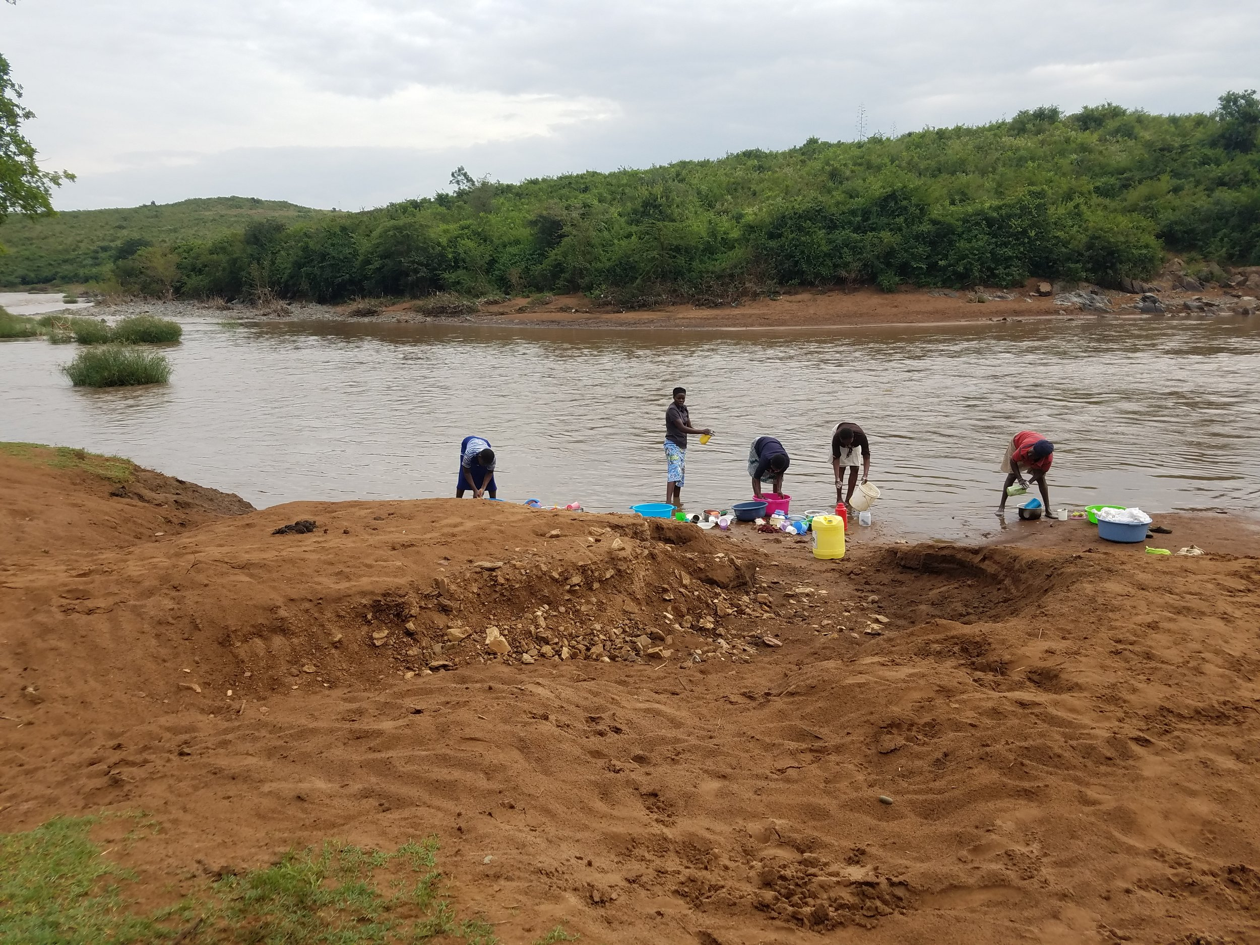 The women and children walk 3-8 hours to reach this river filled with potentially deadly diseases and crocodiles.