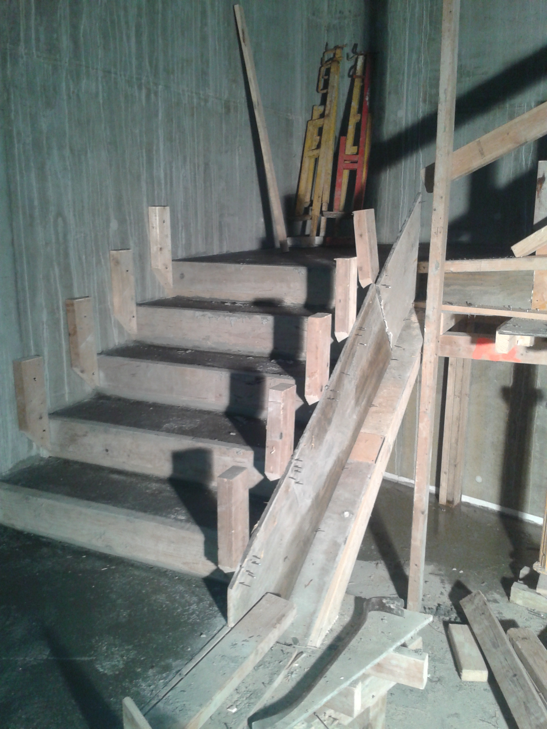 Siding, and stairs - Sins this is a starwell it is concrete wall at one side and only needed to make one siding, when we make the forms that makes to stari we take a 2x6 or 2x8 depends on the high off your Unit height when we cut them with 45 degree angle to the same height at the unit height when u have that 45 degree angle its possible for u to get all the way into the corner off the Unit step finish the concrete. so you make all off them then you nail on this 2x4 behind and fasten the one side to the concrete wall and the other to the siding, make sure to nail it good as you need to be able to walk on them when pouring and finishing the concrete.