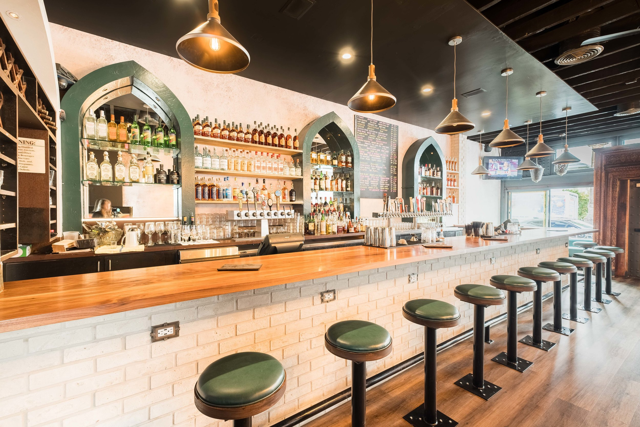 Bar view showing interior with beer taps, sprits and barstool seating