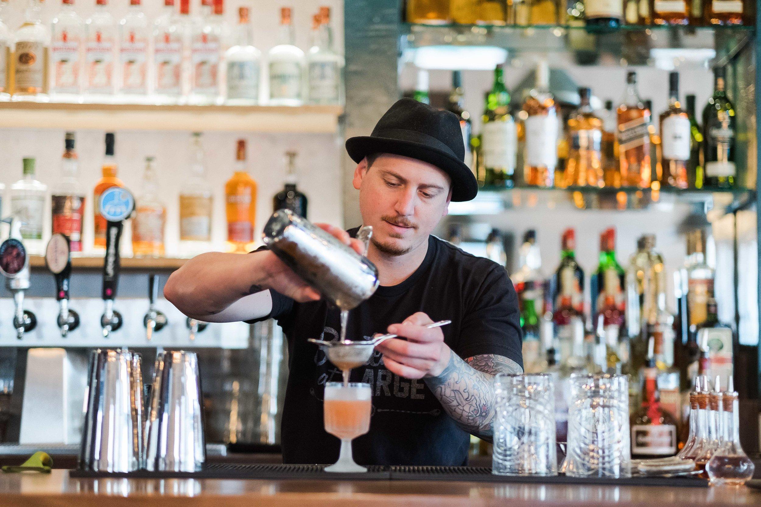 Frank McGrath mixing cocktails at bar