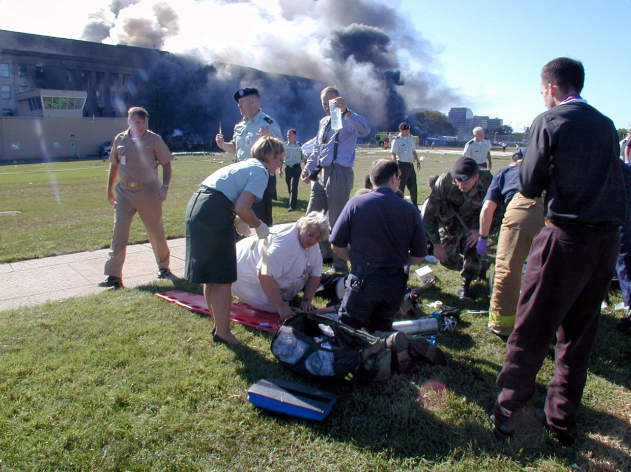 Father Stephen McGraw, far right, prays over a victim of the attack on the Pentagon. (Mark Faram/Army-Navy Times)