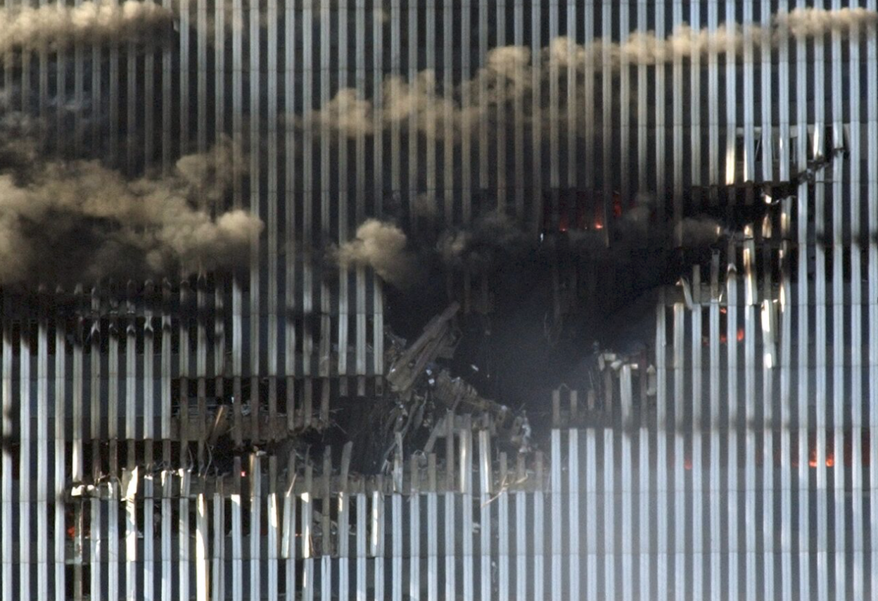 Detail of damage from Flight 11 to the north face of the North Tower of the World Trade Center. A person is barely visible, standing at the bottom of the hole. (Amy Sancetta/AP)