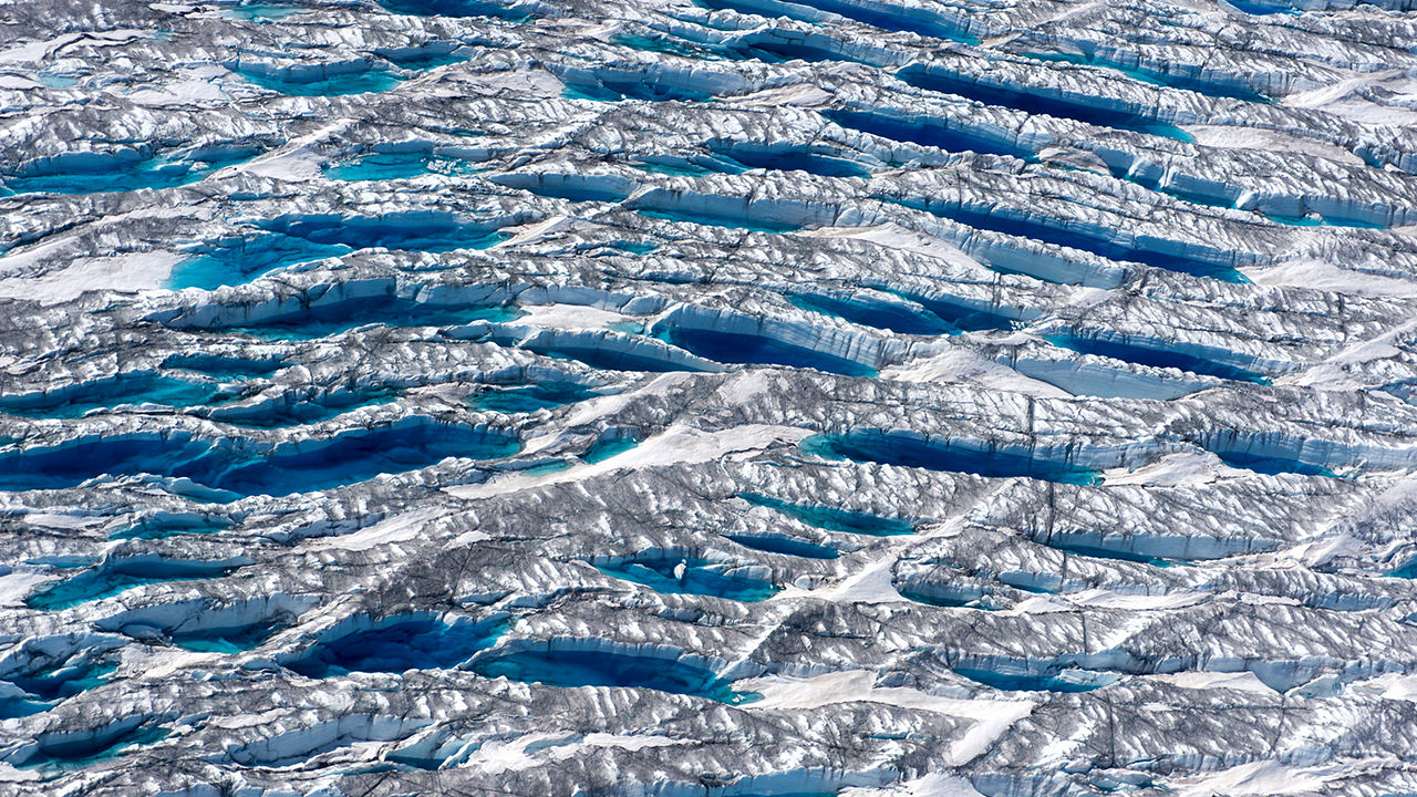 "Ice melting near the edge of the Greenland Ice Sheet, "" while dust and algae darken adjacent ice"".   (Adam Lewinter, Extreme Ice Survey)"