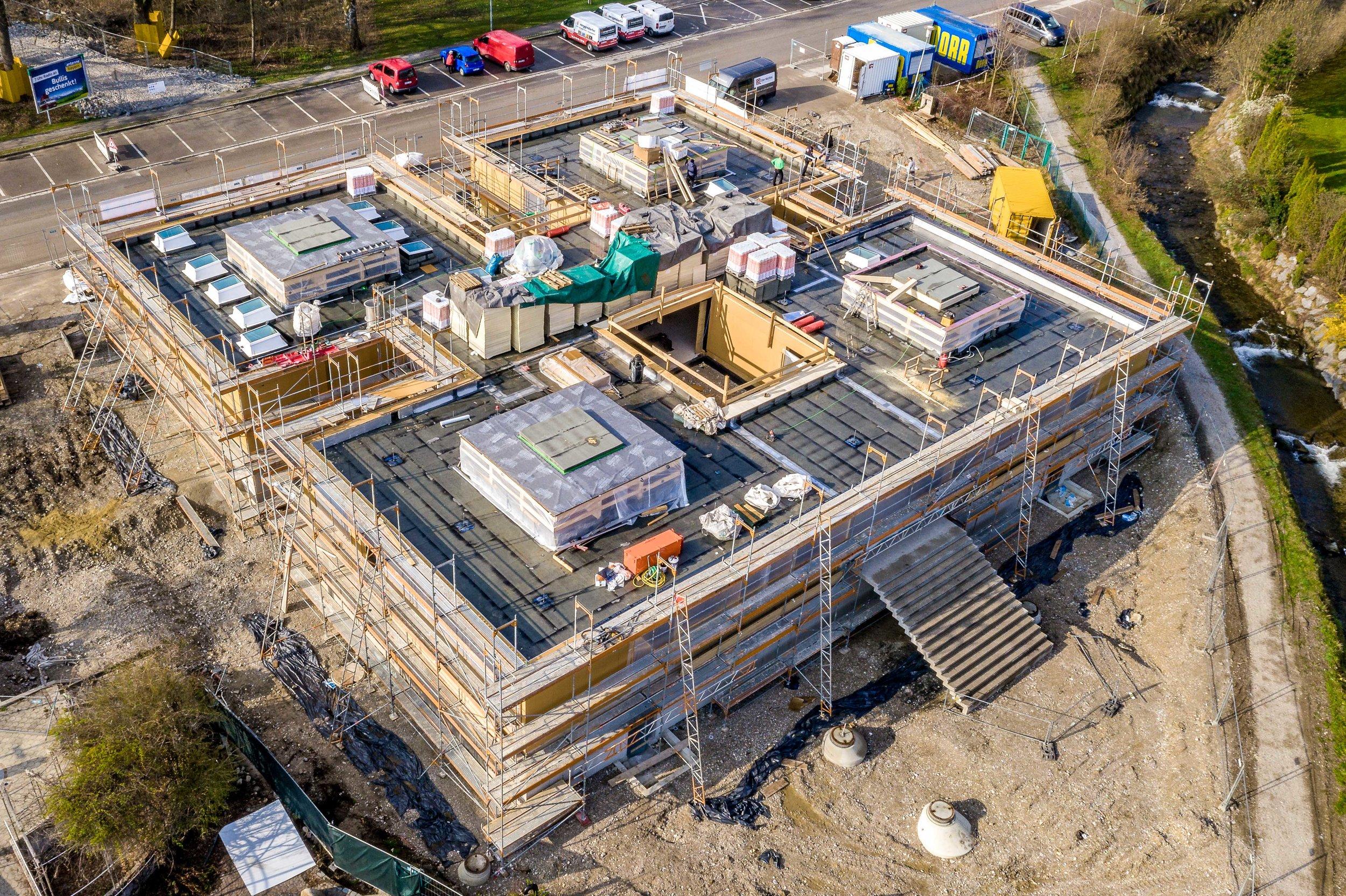 ROHBAU ABGESCHLOSSEN - Der Neubau schreitet voran: Nachdem in den letzten Monaten das Fundament gelegt und die Wände des Badehauses gezogen wurden, steht nun das Dach! Auch im Erdgeschoss werden derzeit die letzten Rohbauarbeiten abgeschlossen und die Fenster eingesetzt. Somit startet bald die nächste Etappe: Der Innenausbau mit den Trockenbauarbeiten. Während im Untergeschoss bereits die Arbeiten für die Heizungs-, Lüftungs-, Elektro- und Sanitäranlagen begonnen worden sind, folgt demnächst das Erdgeschoss. Somit ist klar: Der Neubau ist im Zeitplan und das gesamte Jod-Schwefelbad-Team freut sich auf die nächste Etappe!