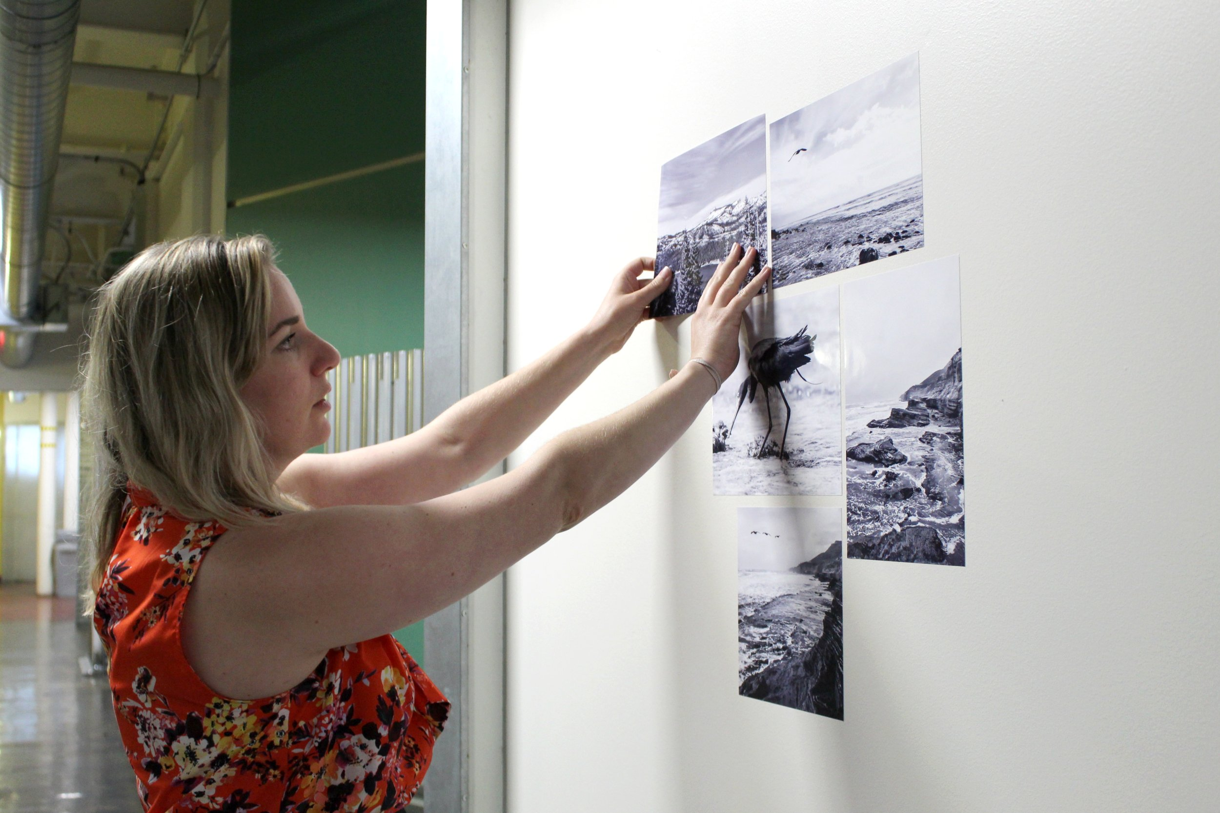 Megan demonstrates to open house visitors how Pinless Pics can be placed and repositioned without damaging the walls.
