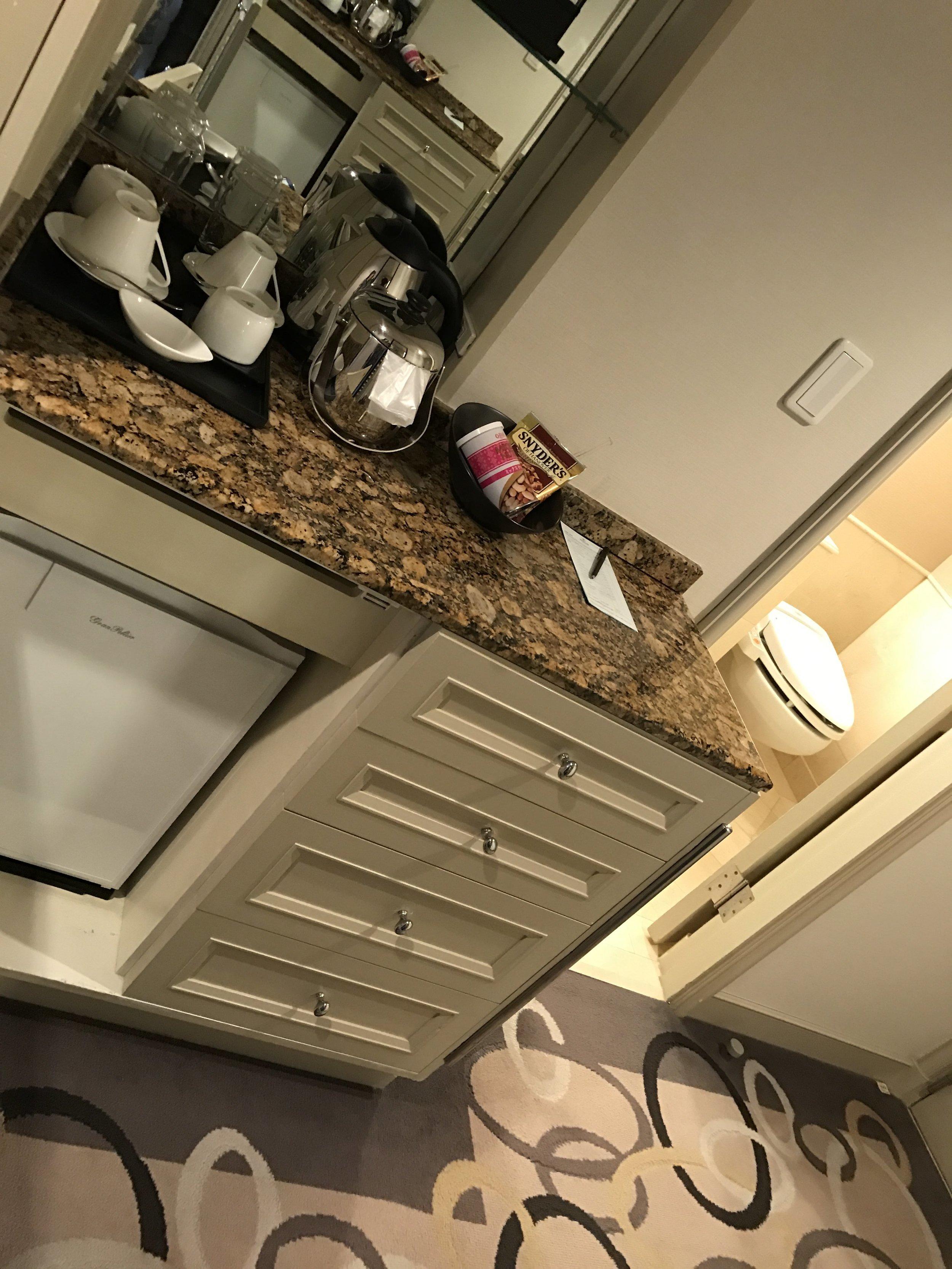 Hallway counter with coffee and tea maker and mini fridge