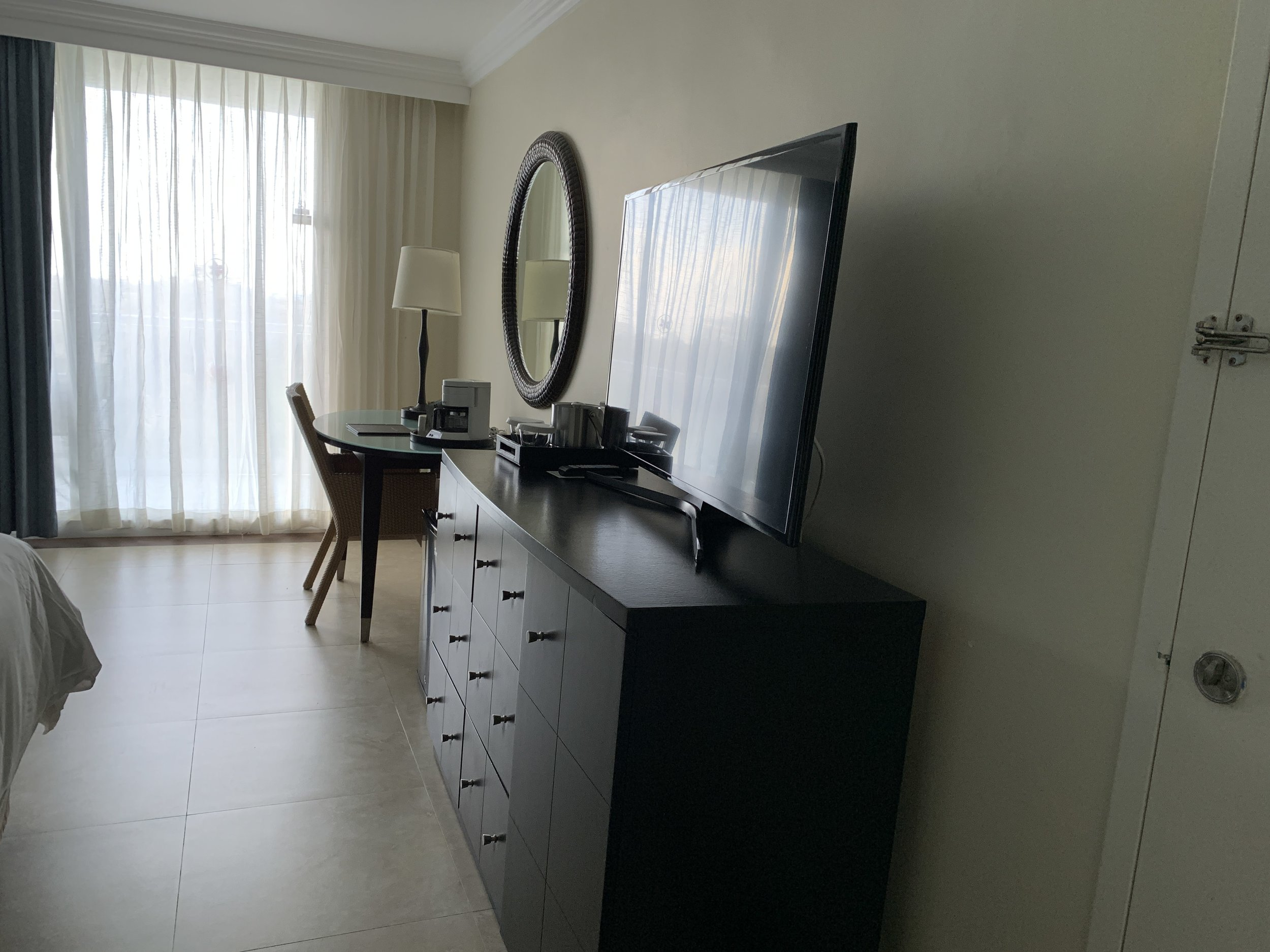 Connecting room with smart TV (Netflix capabilities), dresser drawers, and desk with reading lamp.