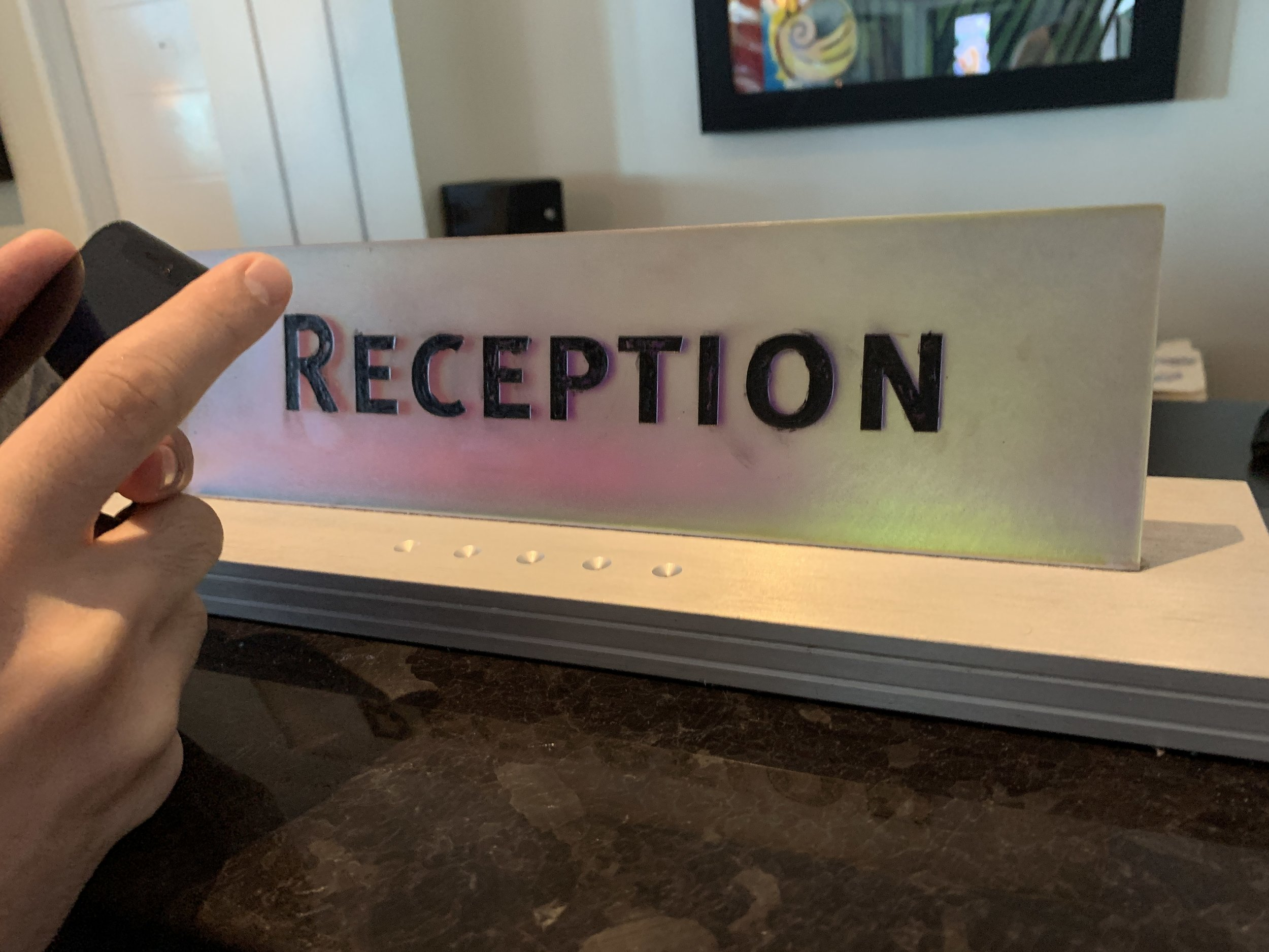 Close up of the Reception Desk sign. It looks like it was colored in with a ball point pen