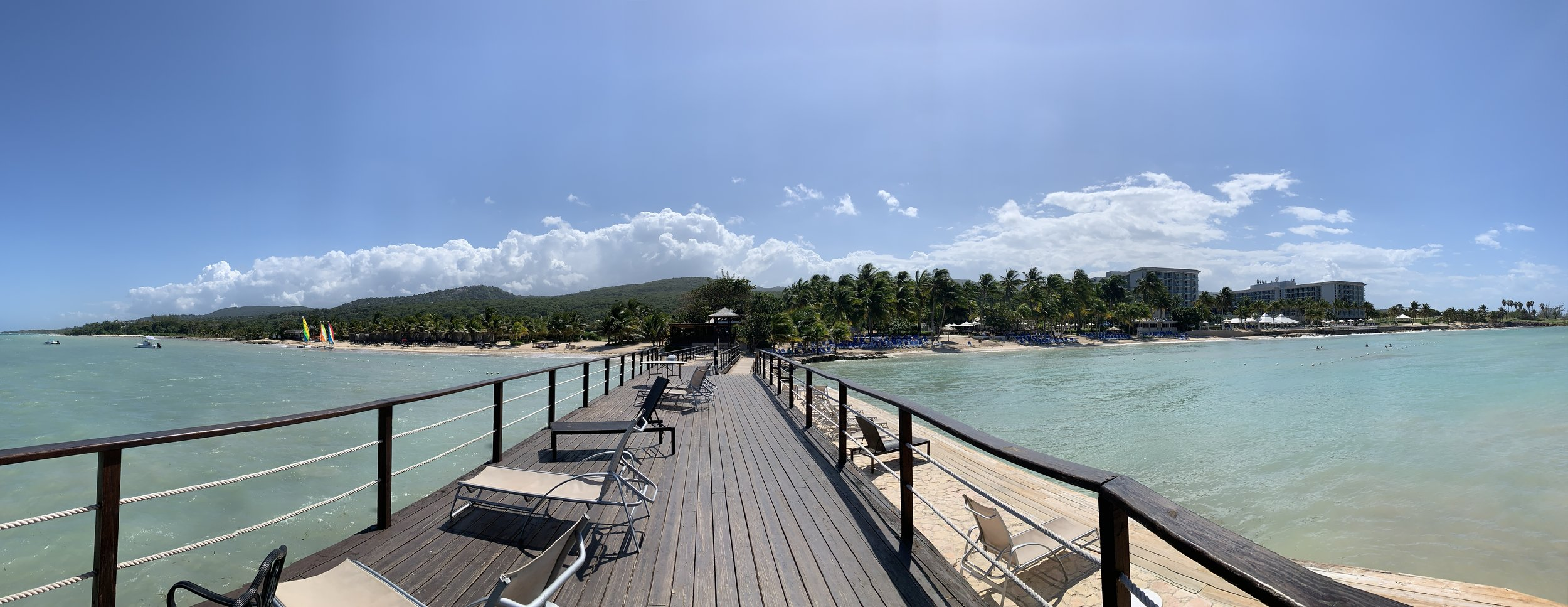 Panoramic view from the resort pier. To the left is the quiet beach, cabana rentals and activity rental desk. To the right is the pools and resort.