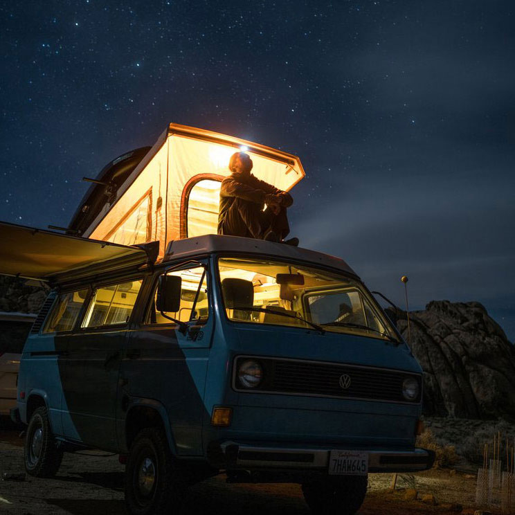 Person sitting on a VW camper van looking at the stars