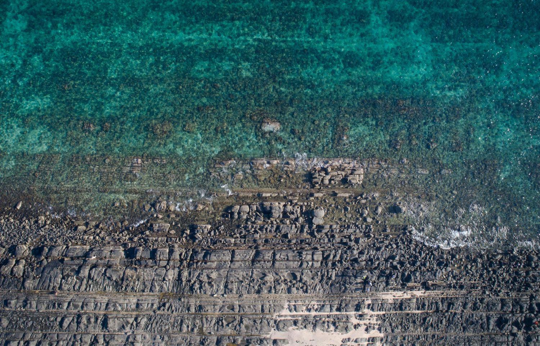 Rocky shoreline against a clear green sea
