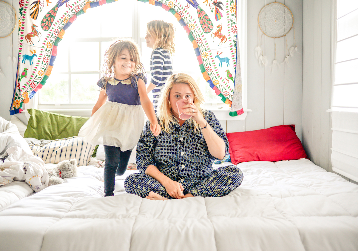 Funny mom drinking coffee on bed with children running around her.