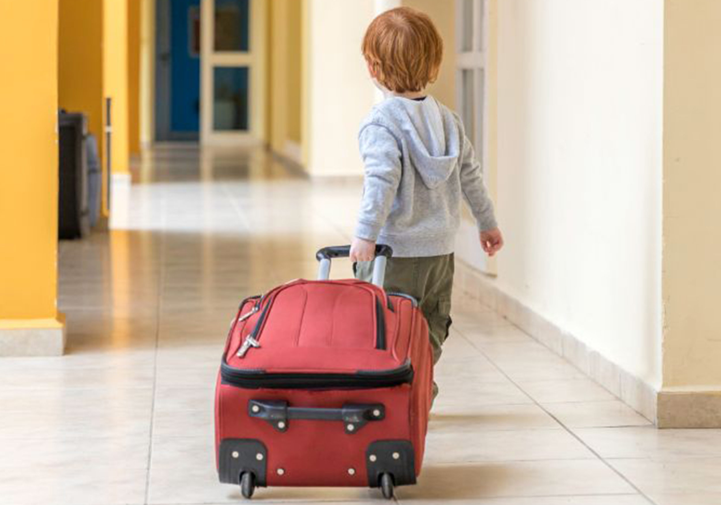 Holiday travel with kids: 11 tips for a stress free trip. Boy dragging suitcase by its handle.