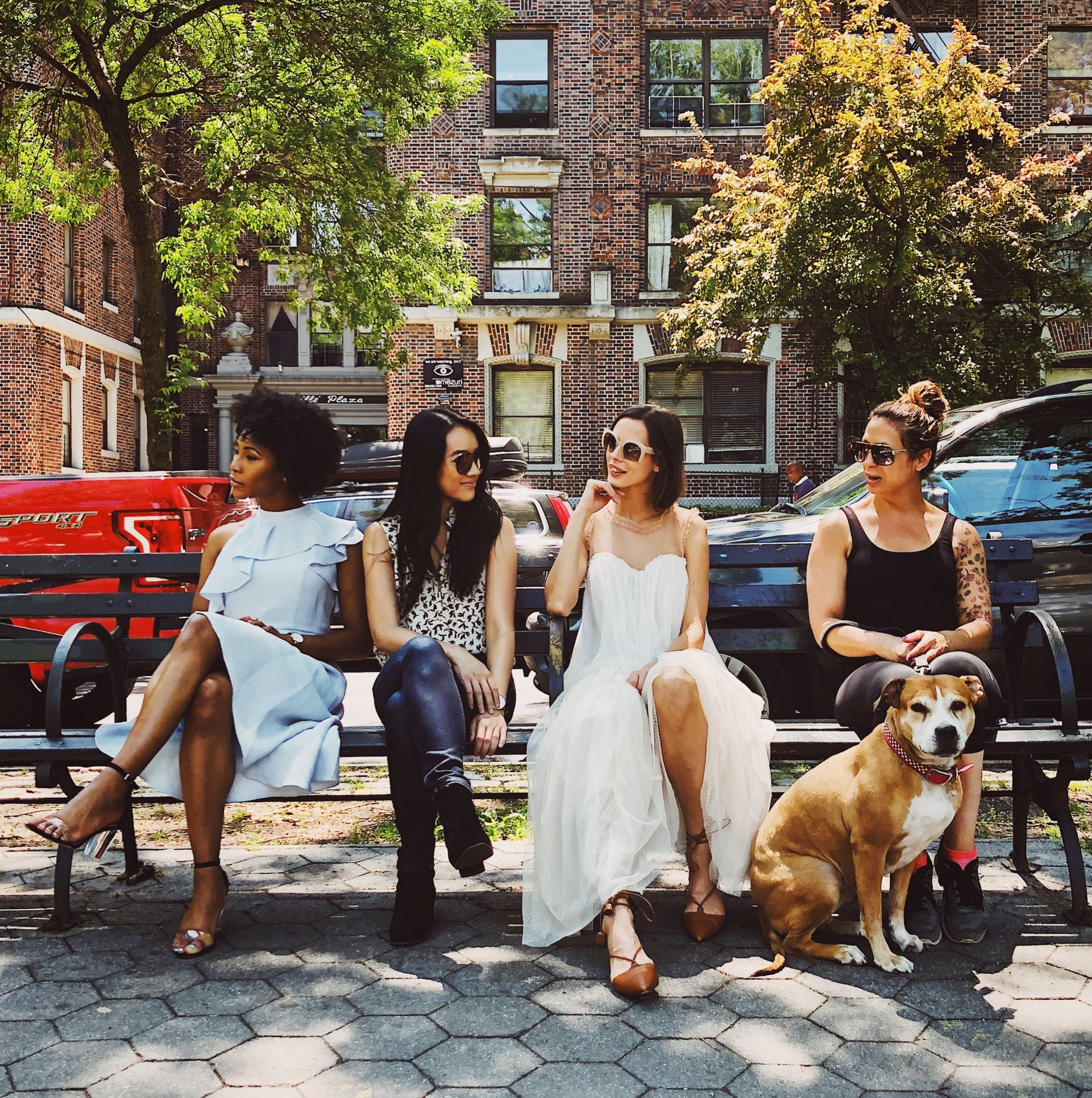 Four women on city park bench talking.