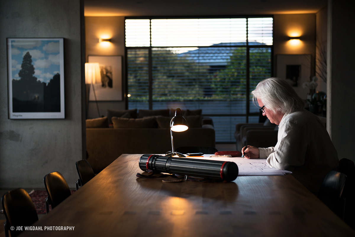 Portrait of Architect working on drawings with a lamp and table