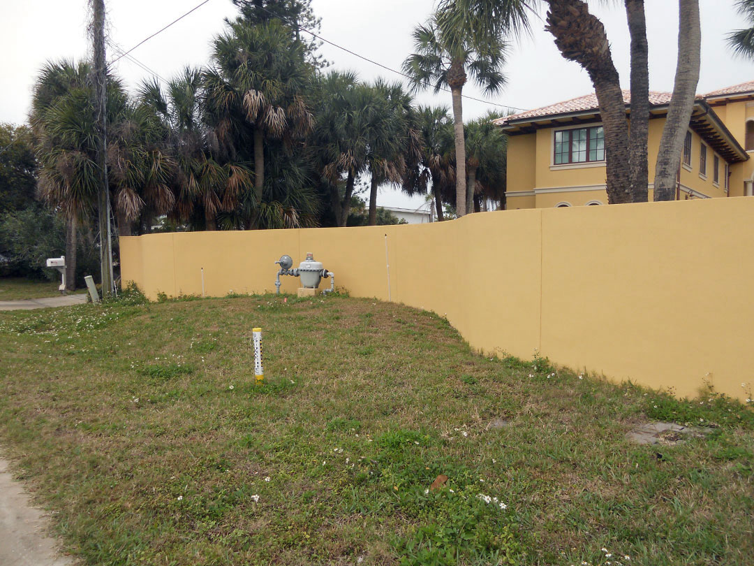 Before - this dull painted wall exposes utilities and is lined with dying grass
