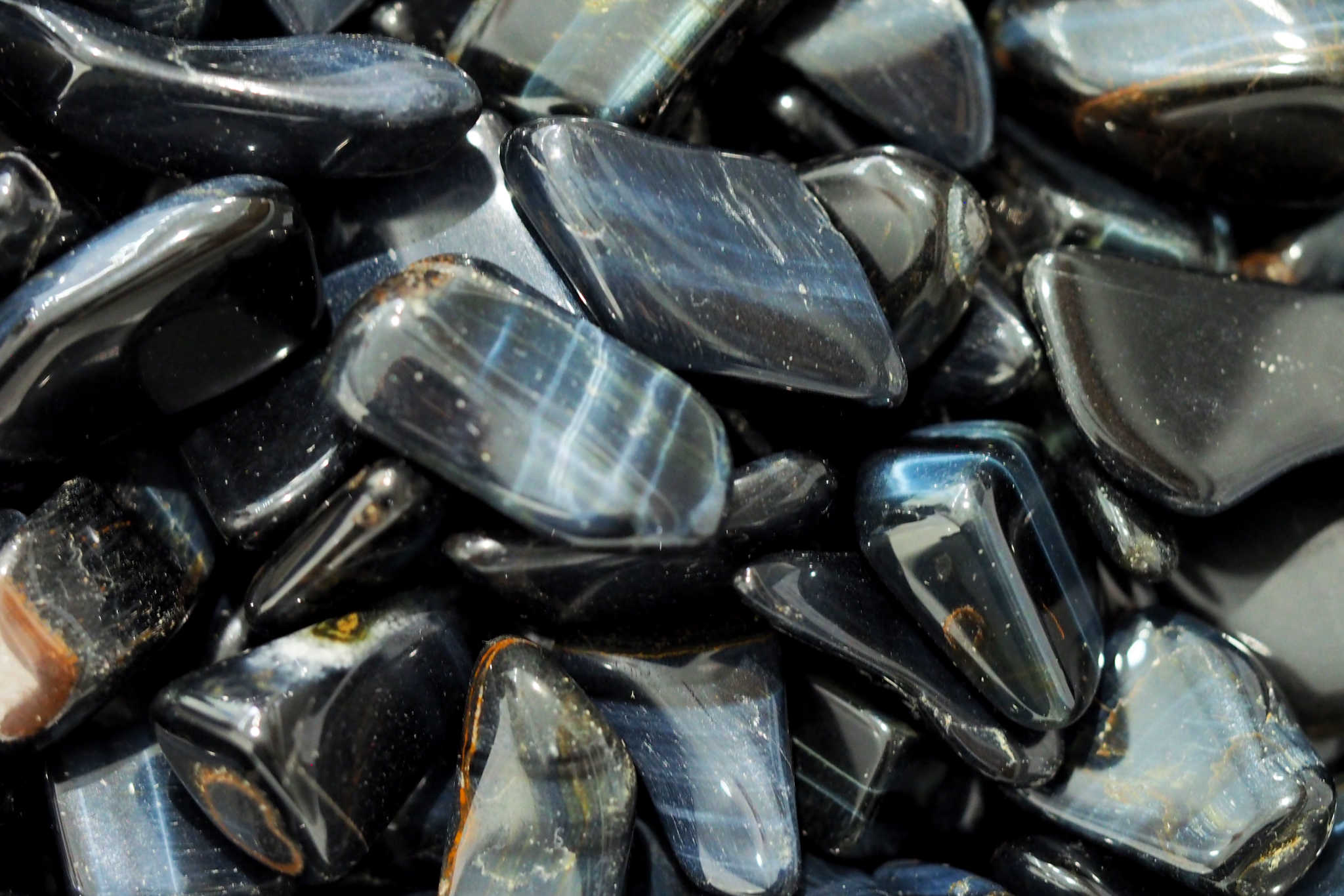 BLUE TIGER'S EYE - A chatoyant gemstone, this variety of Tiger's Eye displays a beautiful silky lustre and shimmery blue-dark blue banded hue.Origin: South Africa, Brazil, India, Burma, USA & Western Australian.Properties: Reduces stress, increases calm and eases anxiety. Aids in fatigue and depression, encourages emotional balance.