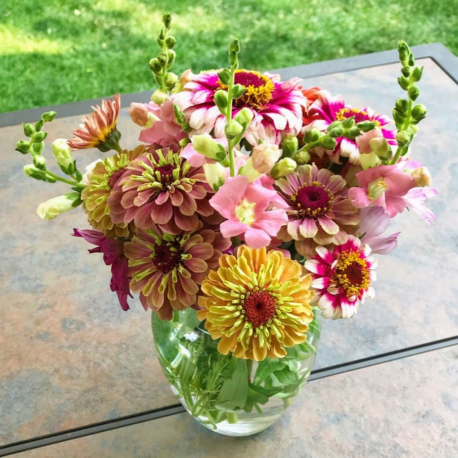 Zinnias and snapdragons in flower arrangement. Consider Bighorn Blooms for all your florist needs.