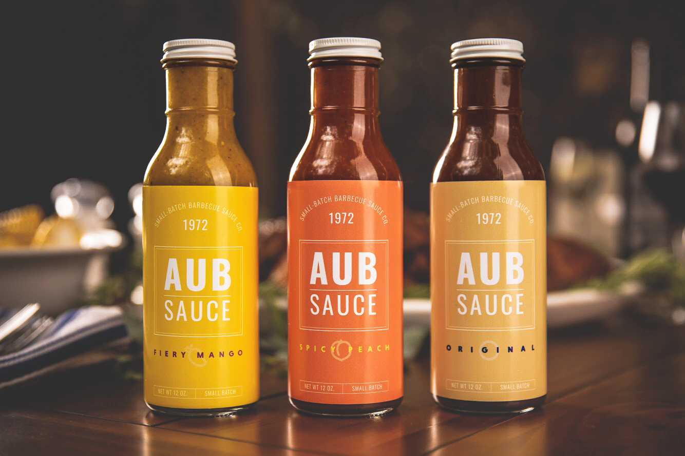 it's aubsome! - AubSauce is a line of small-batch, artisan barbecue sauces. AubSauce features three sauces — Spicy Peach, Fiery Pineapple Mango, and Original Barbecue. All contain a mixture of spicy, sweet, and savory flavors!