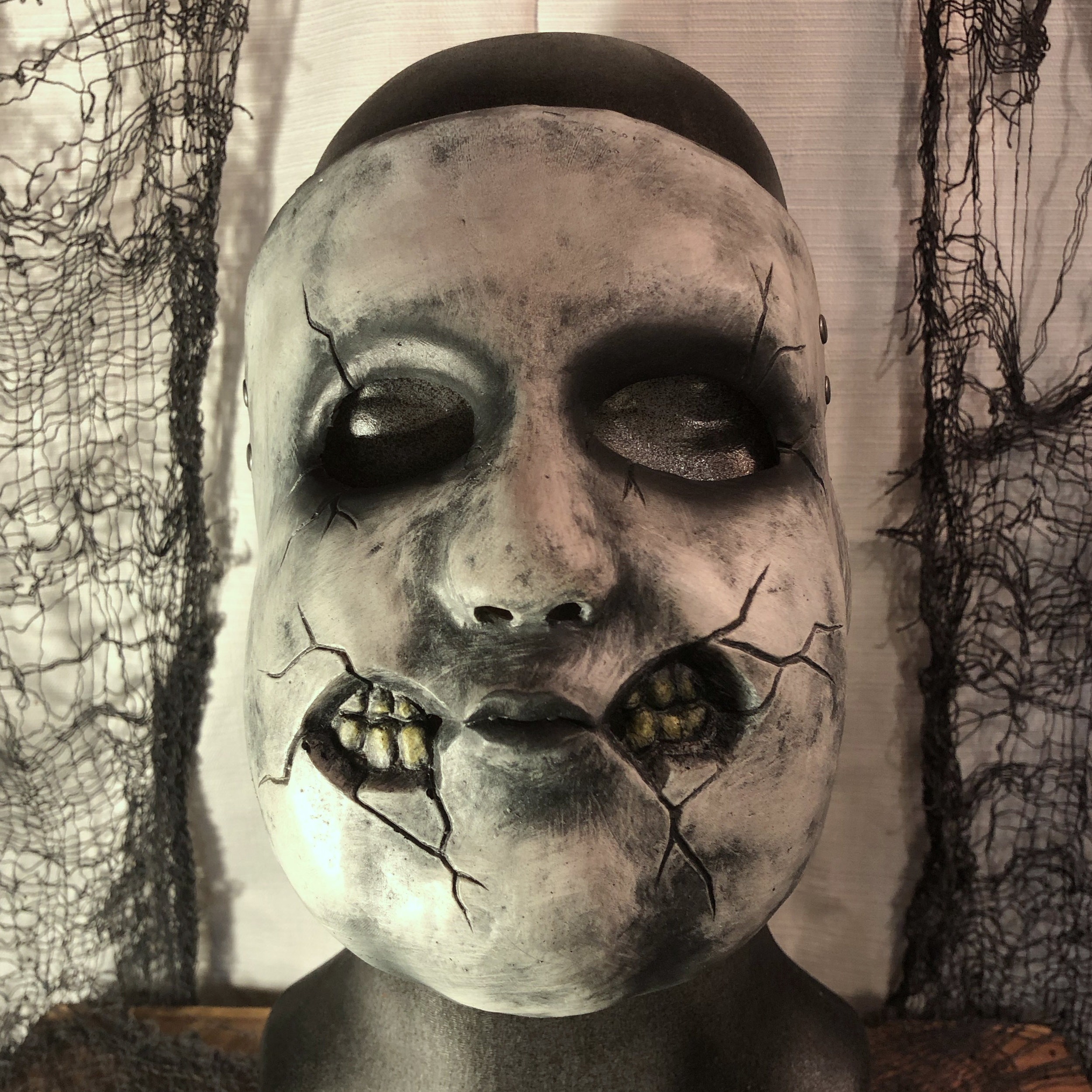 Dolly    $80.00   This broken doll mask will fit most adults, but is on the smaller side.  When worn by a large man, the juxtaposition can be quite disturbing.  100% Natural Latex Mask