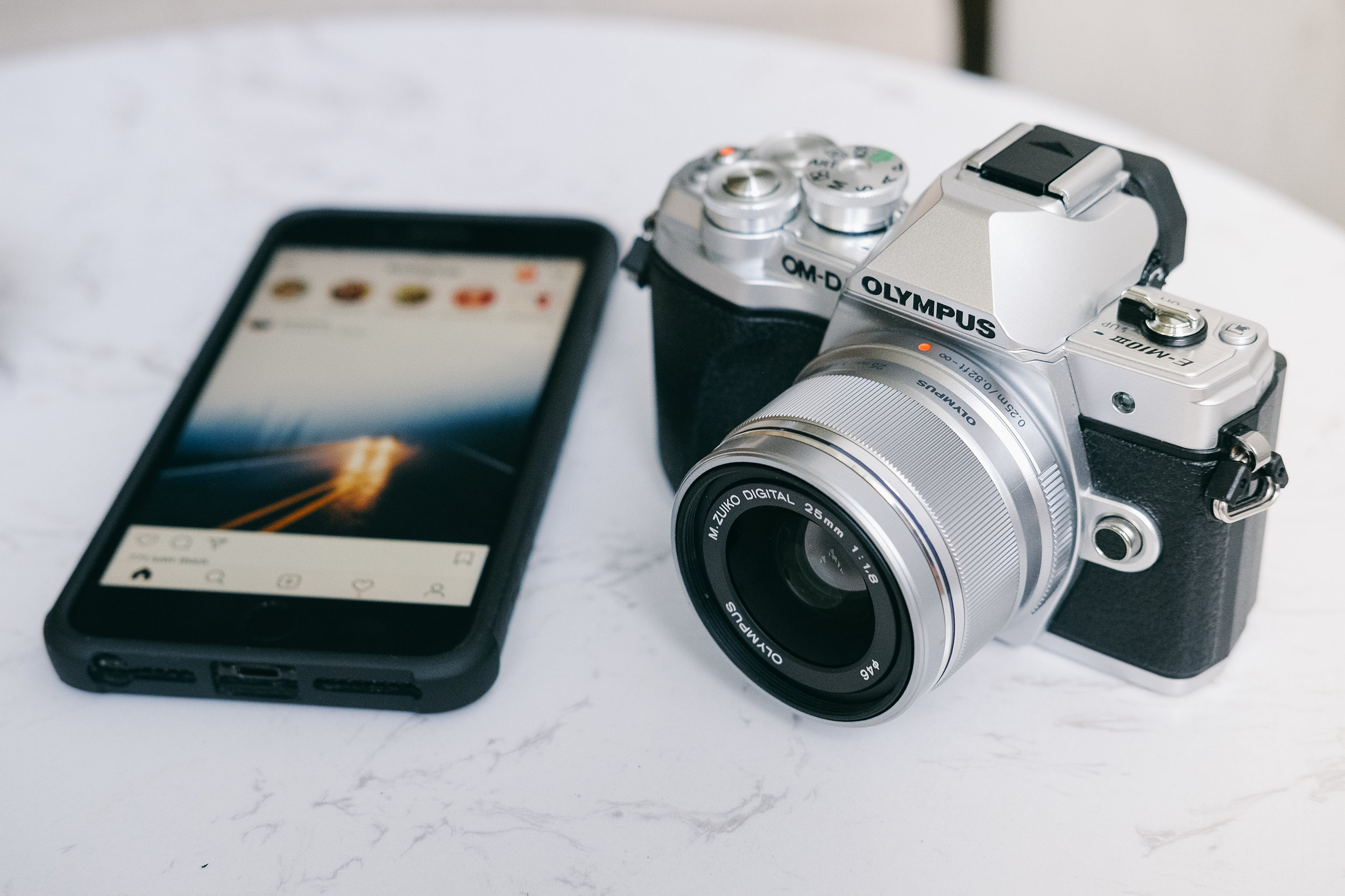 image of phone with instagram app open and an olympus camera next to it