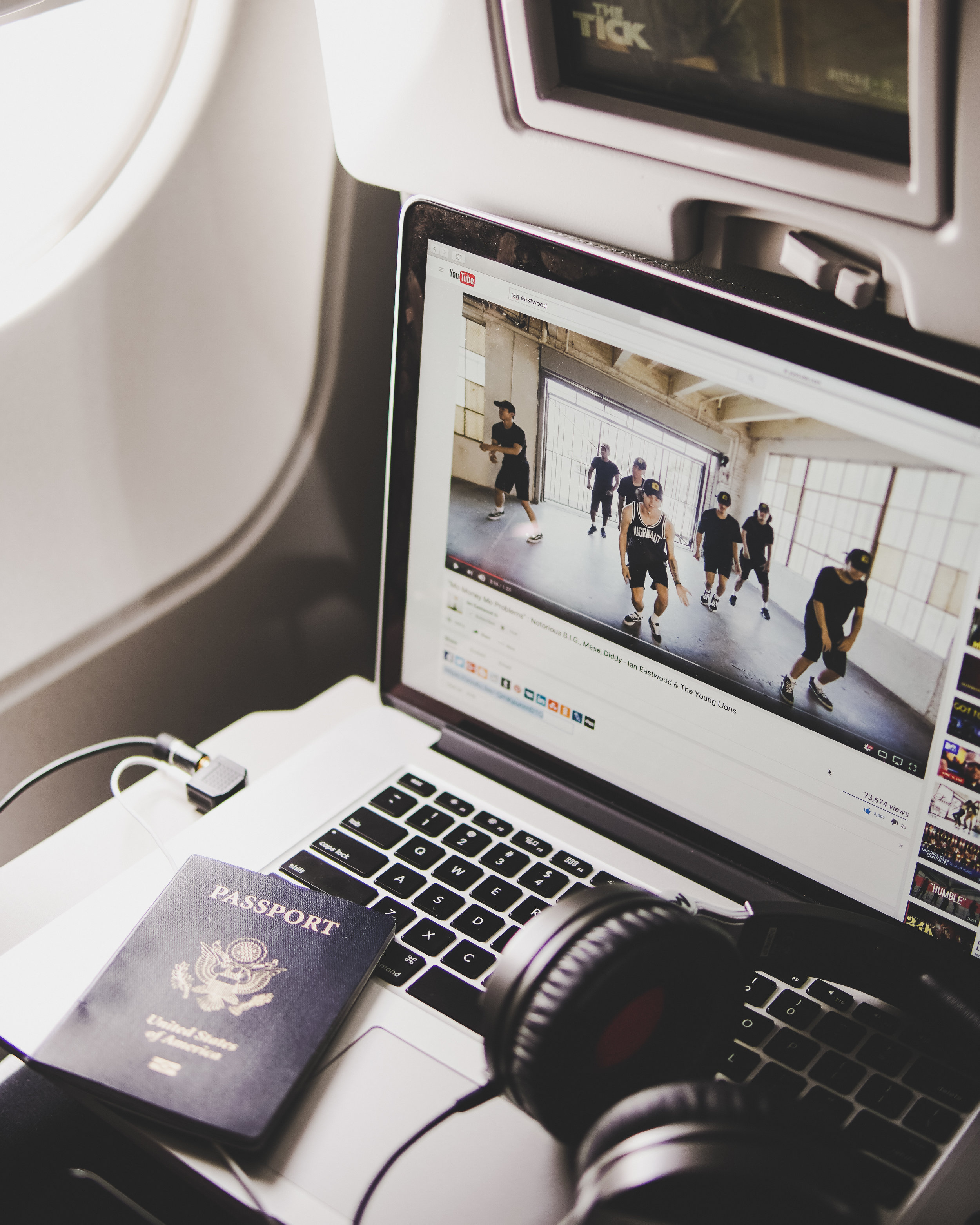 laptop with youtube video of people dancing a passport and headphones image