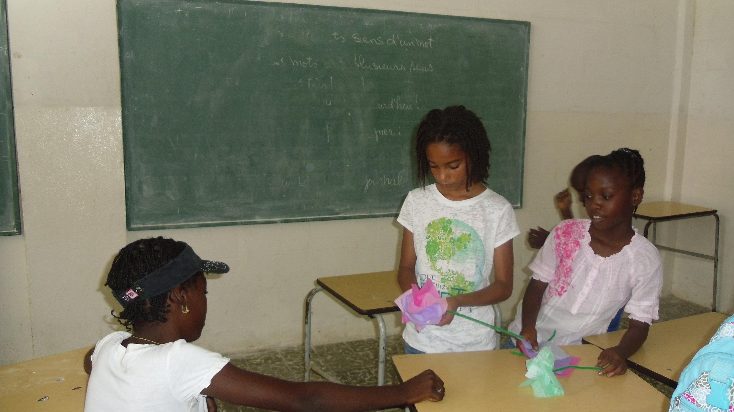 Zia teaching girls in Haiti how to make paper flowers.