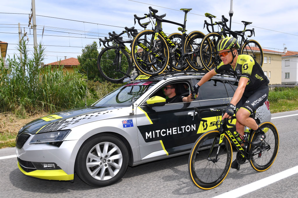 Chris Juul-Jensen takes a bottle from a Mitchelton-SCOTT directeur sportif