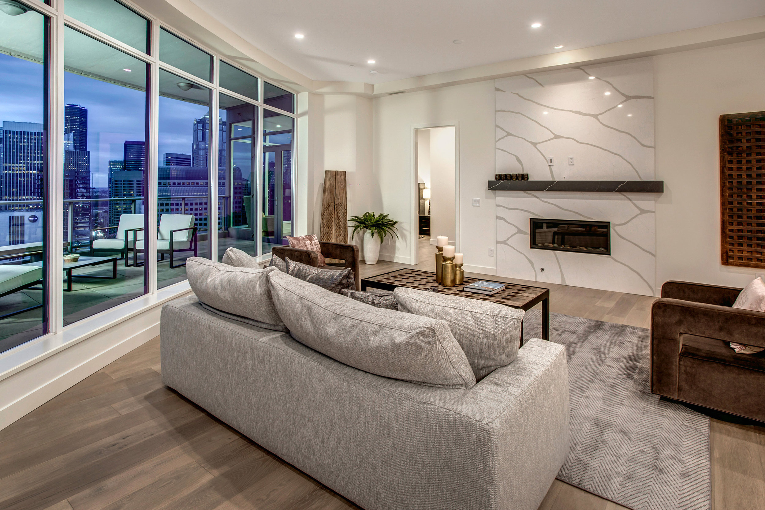 Spectacular great room with southeast facing views of the city and Cascade mountains, Heat & Glo gas fireplace with River Rock Design Media, Calacatta Quartz wall accent, and a Sorano honed finish Quartz mantel.