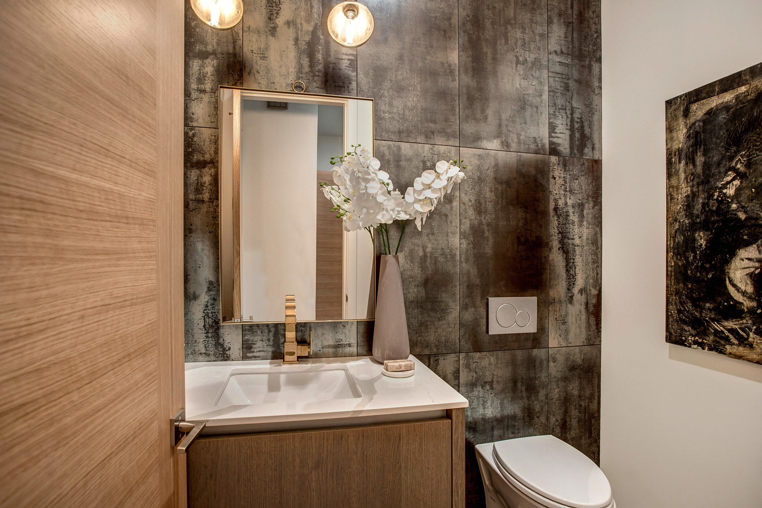 Powder room featuring floor to ceiling Copper Corten metallic tile accent wall with Restoration Hardware Aged Brass faucet and bath hardware.