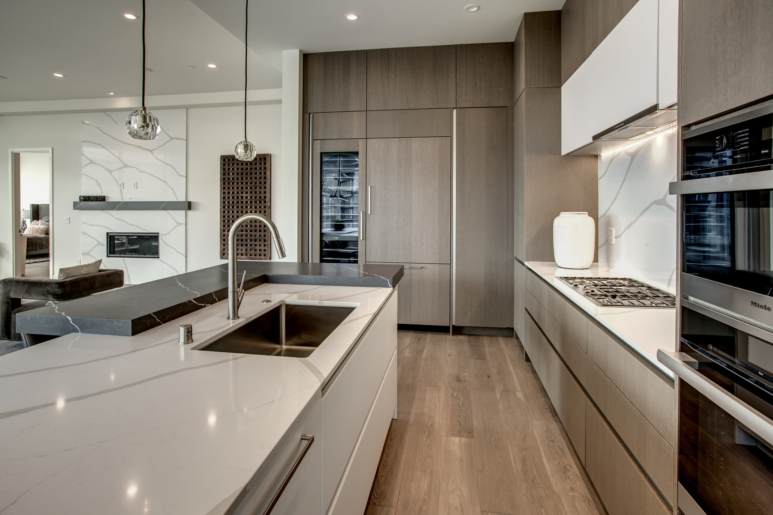 The kitchen is equipped with Miele appliances and includes an espresso maker, wine tower, and three ovens.