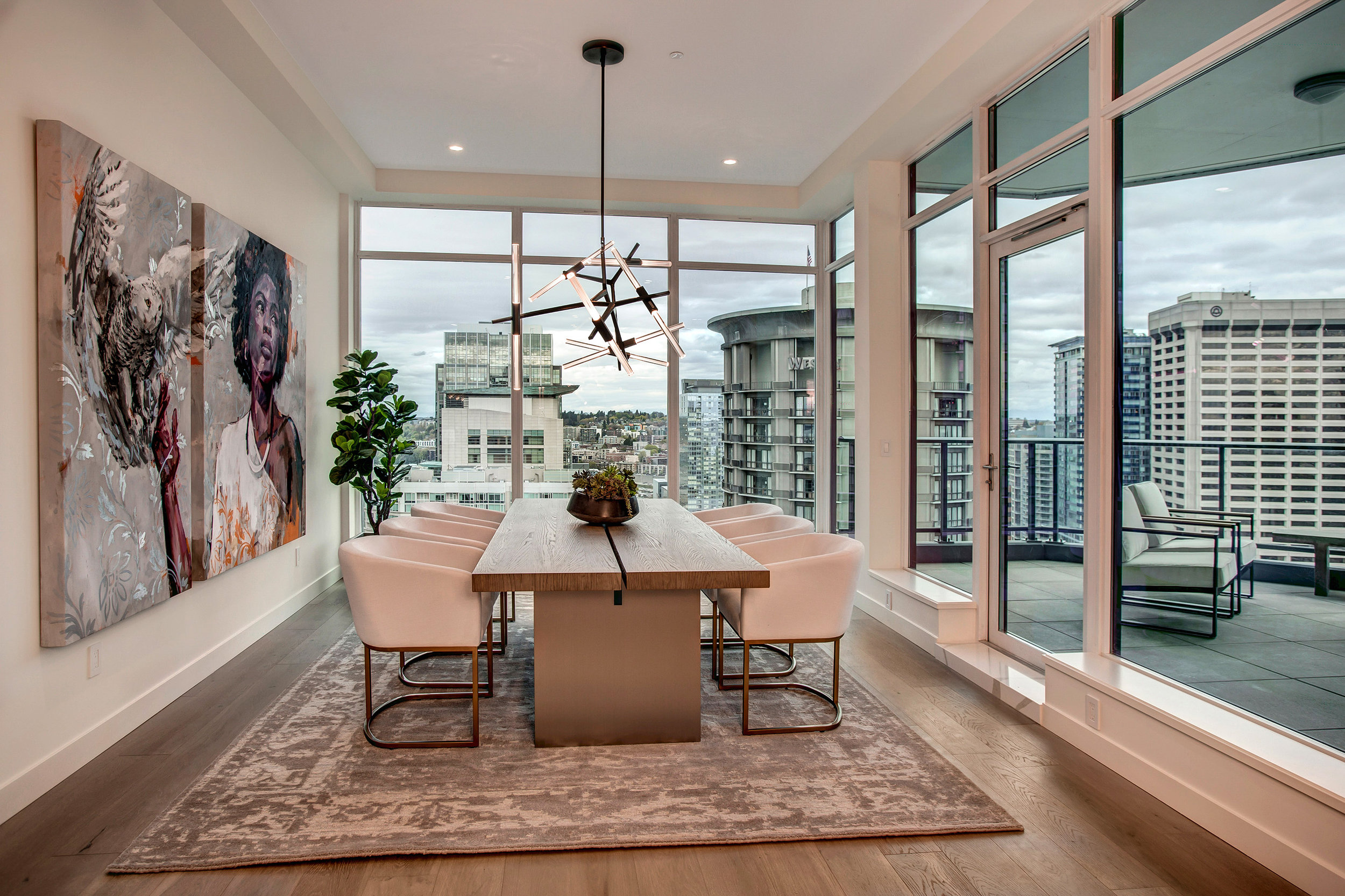 Bright and dramatic dining space featuring floor to ceiling windows with southeast facing views and access to covered balcony.