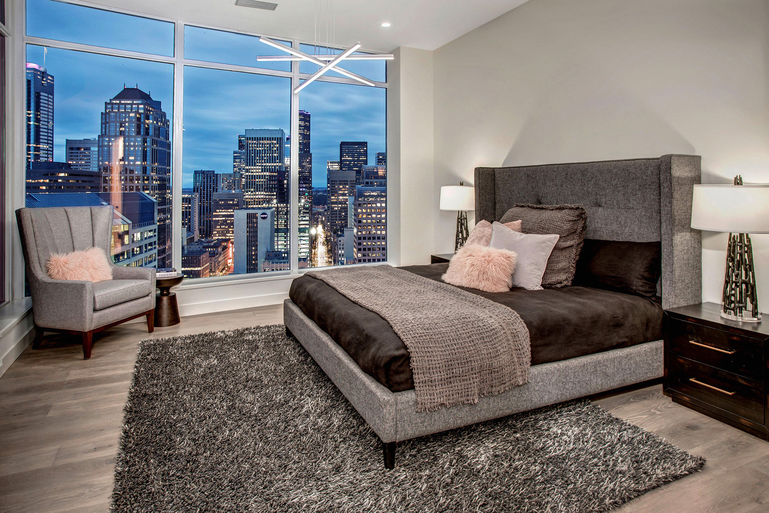 Master bedroom at dusk with glittering city views.