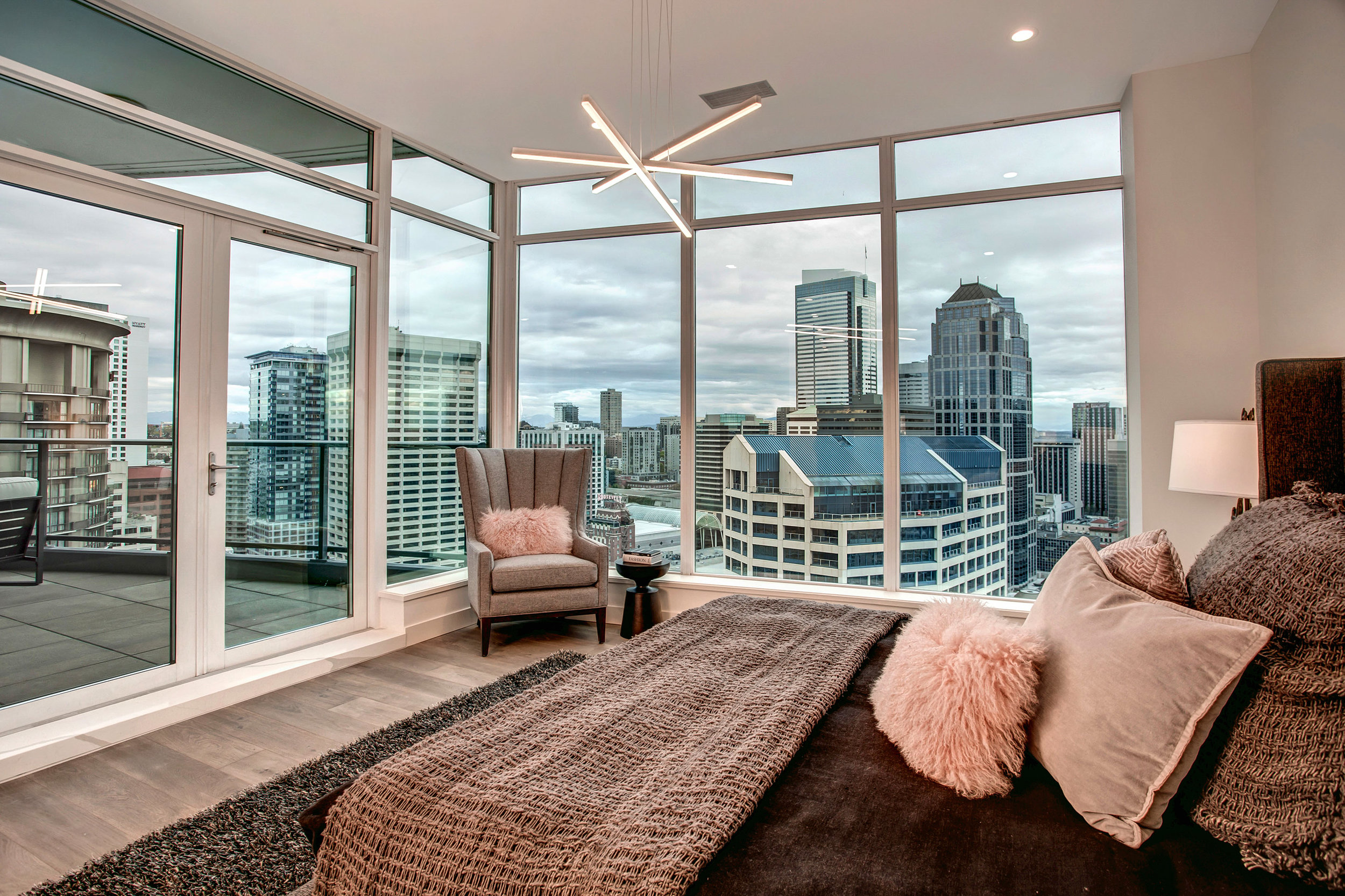 Master suite with floor to ceiling windows, dramatic city views, and access to the covered balcony.