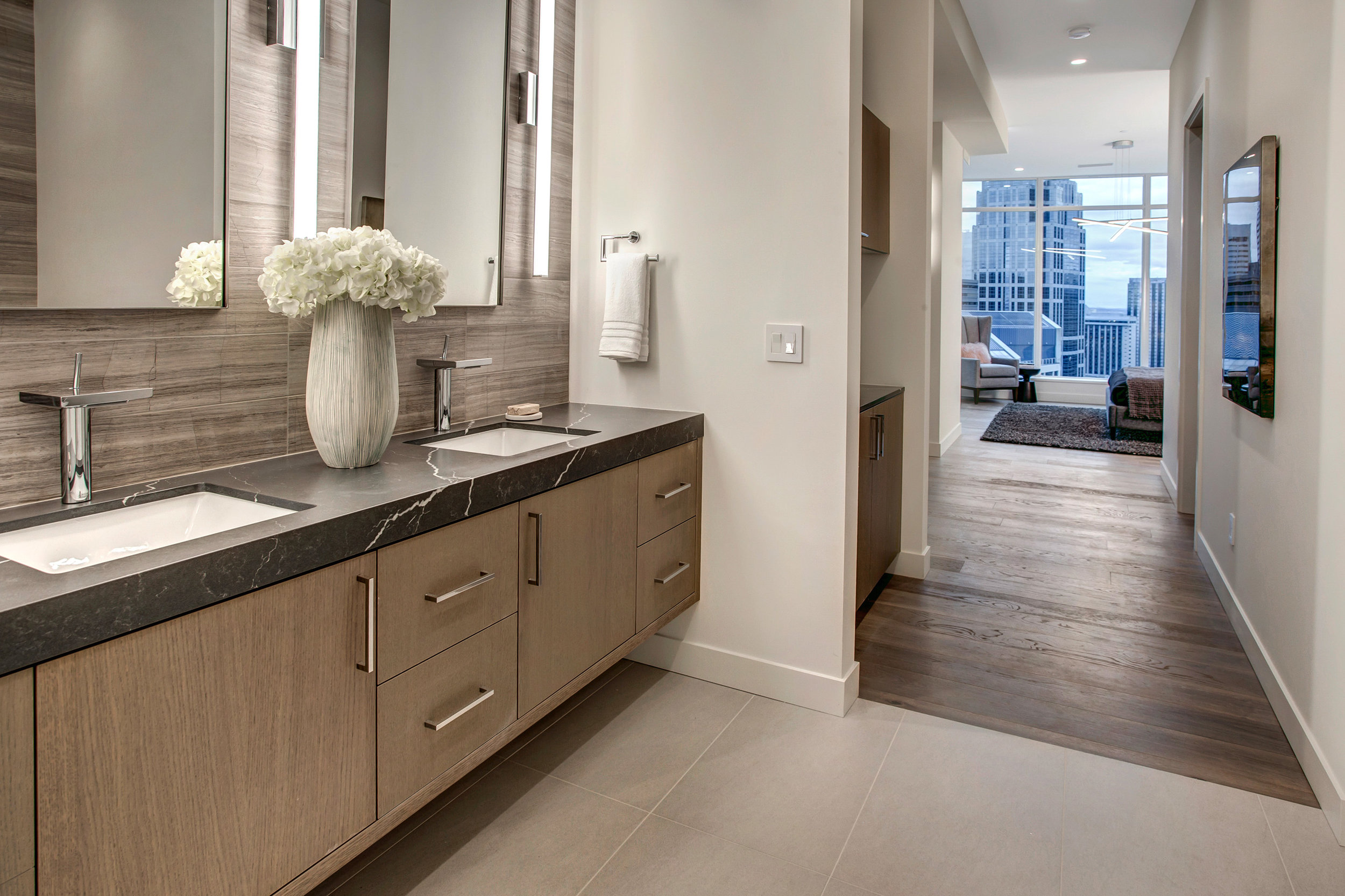 Master suite includes a built-in coffee nook, large walk-in closet, dual sink vanity with Hansgrohe Axor waterfall faucets, honed finish Quartz countertop, and Marble tile accent wall.