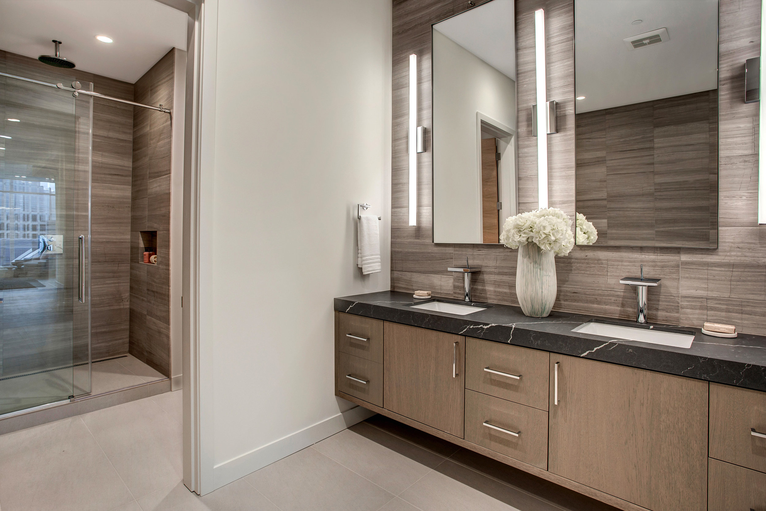 Master bathroom shower includes a Transcend sliding door, Hansgrohe Axor hand and rain shower heads, Thermostatic shower, linear shower drain, and floor to ceiling Marble tile.