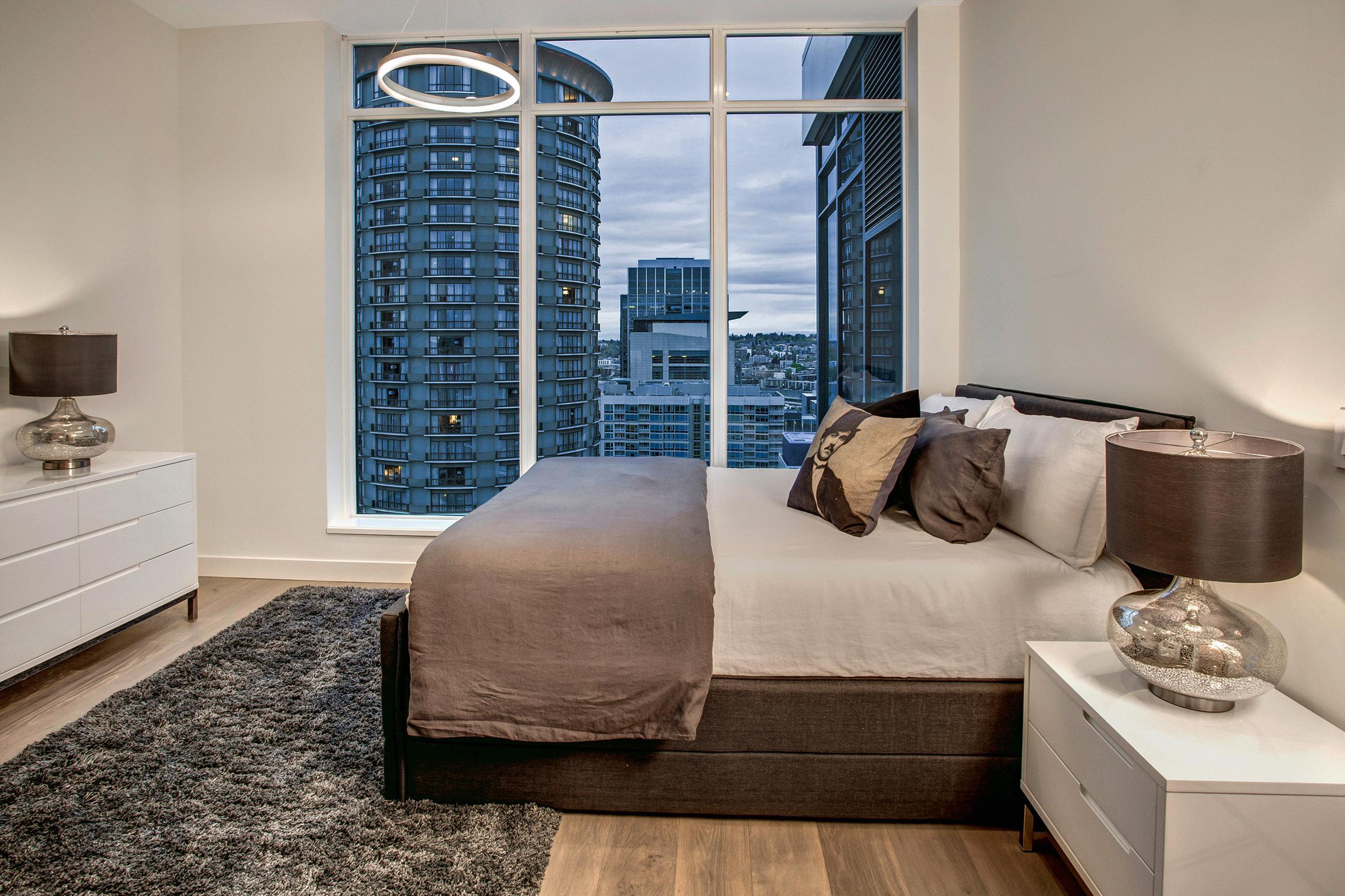 Guest room with en suite bathroom, floor to ceiling windows, and custom built closet.