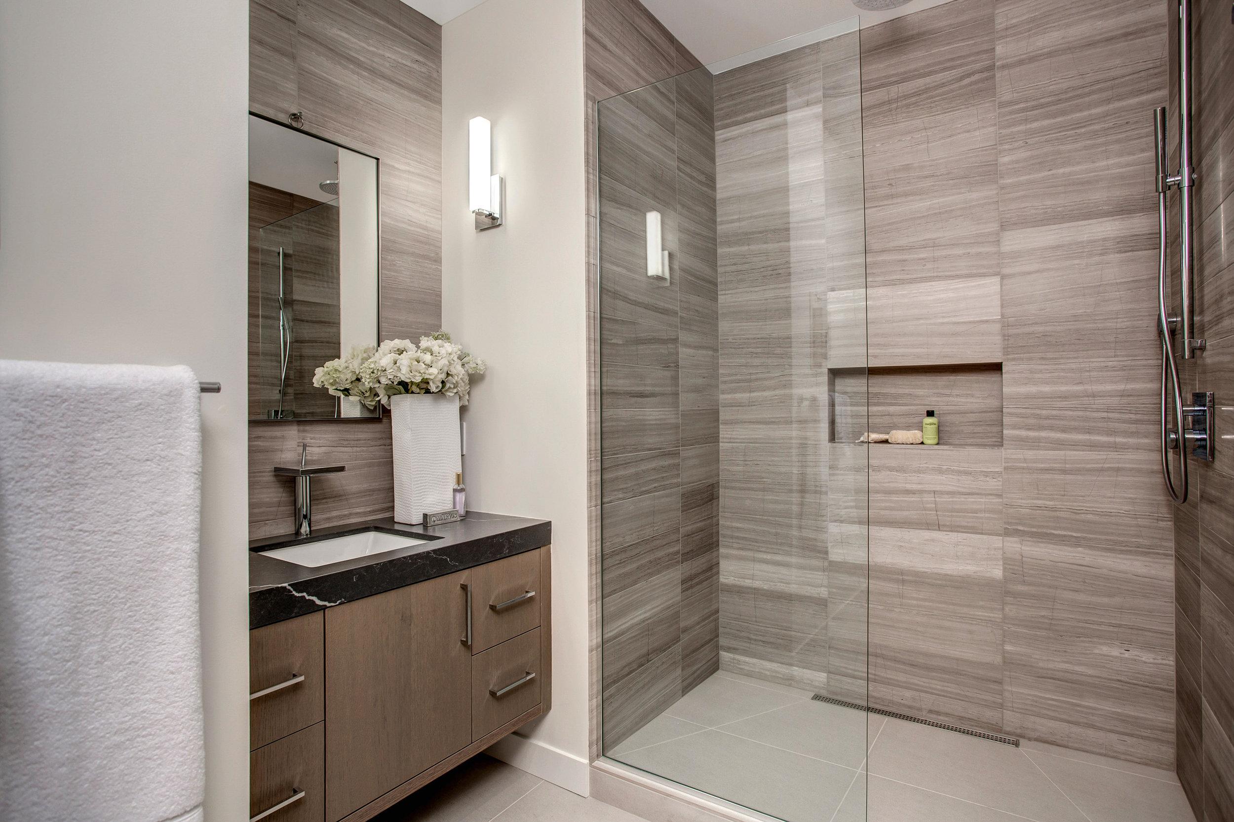 En suite guest bathroom with floor to ceiling Marble tile shower and vanity wall.