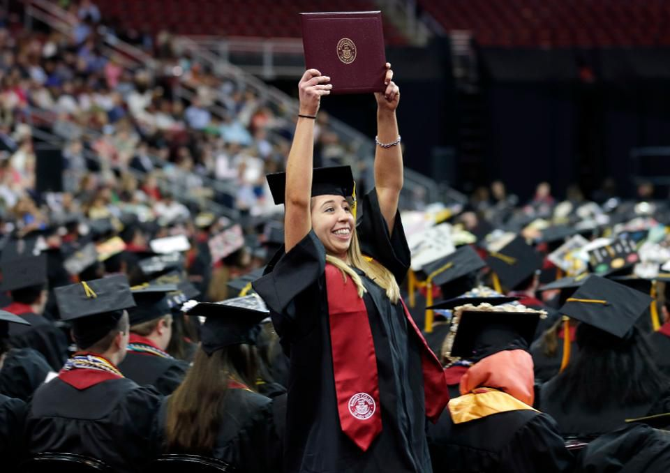 Emma O'Donoghue holds up her diploma as she returns to her seat during an undergraduate commencement ceremony for Ramapo College in Newark, N.J., Thursday, May 10, 2018. (AP Photo/Seth Wenig)  ASSOCIATED PRESS