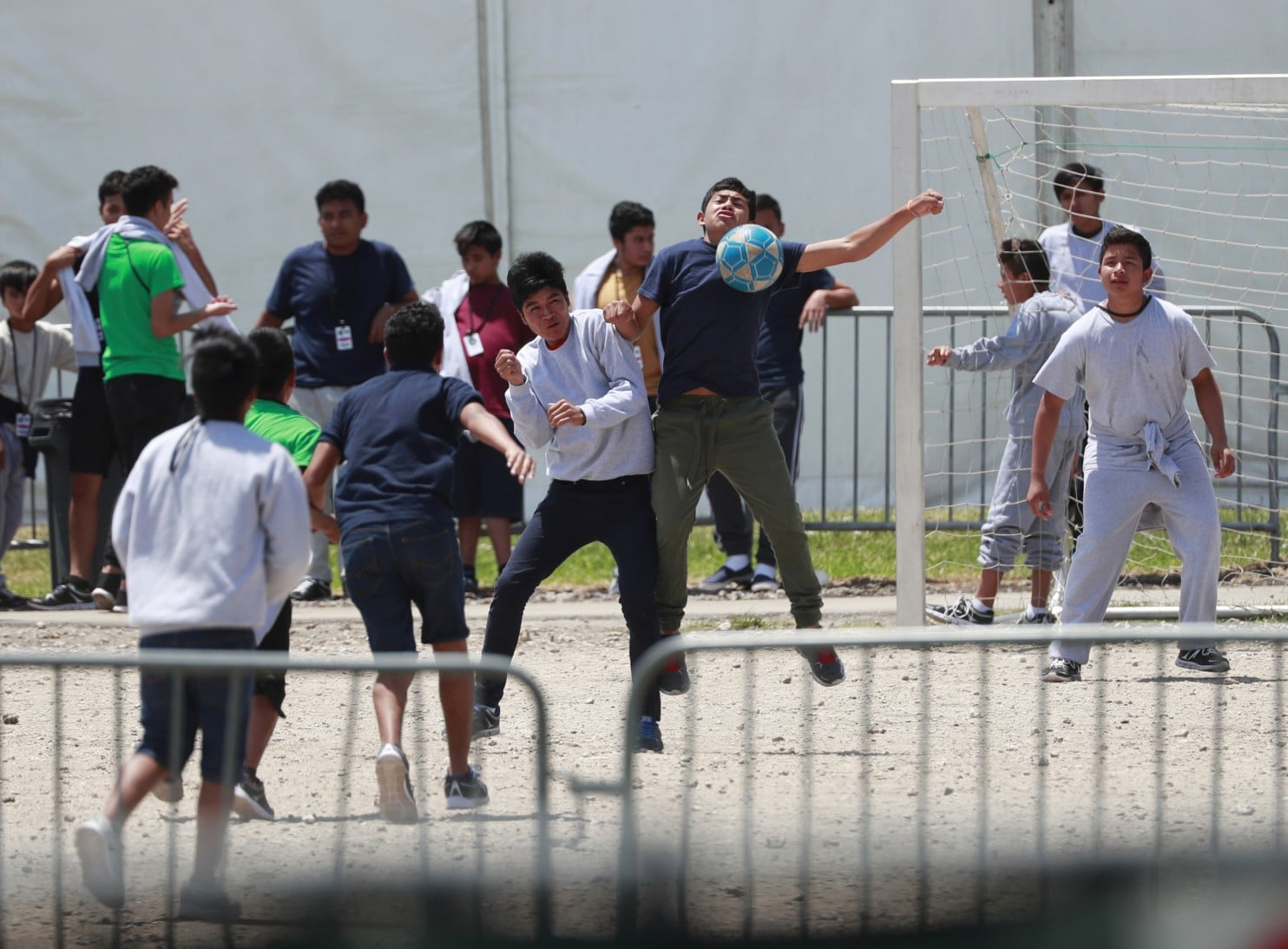 Migrant children play soccer at the Homestead  Temporary Shelter for Unaccompanied Children in Homestead, Fla., on  April 19. The Trump administration is canceling educational and  recreational programs at such shelters, saying the government has run  out of funding for them amid a crush of migrants crossing the border.  (Wilfredo Lee/AP)
