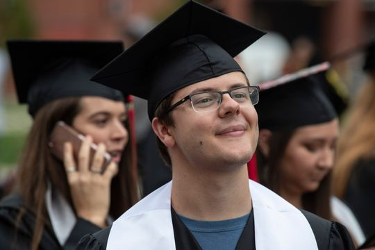 Louisville native Clay Harville, left, walks with fellow graduates  during the Topper Walk at Western Kentucky University. Harville is the  first to graduate from WKU's autism program with a degree in special  education teaching.(Photo: Alton Strupp/Courier Journal)