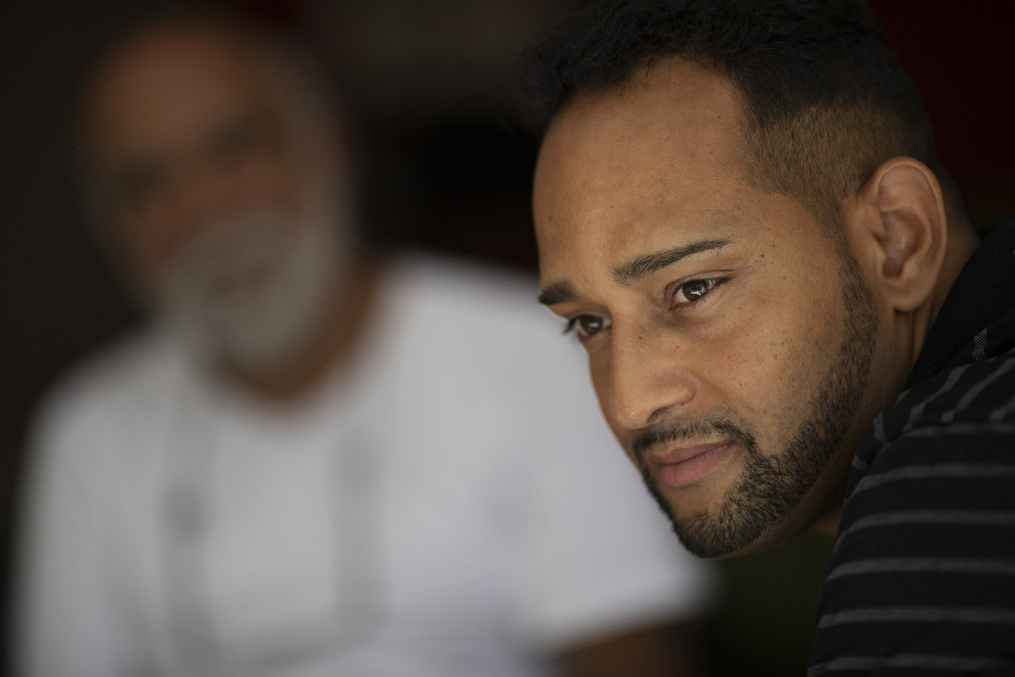 Paul  Fernando Schreiner, right, sits next to Segisfredo Silva Vanderlai, a  pastor who has been lodging Schreiner since a few weeks after his  arrival, in Niteroi, Brazil, on April 11, 2019.Leo Correa / AP file