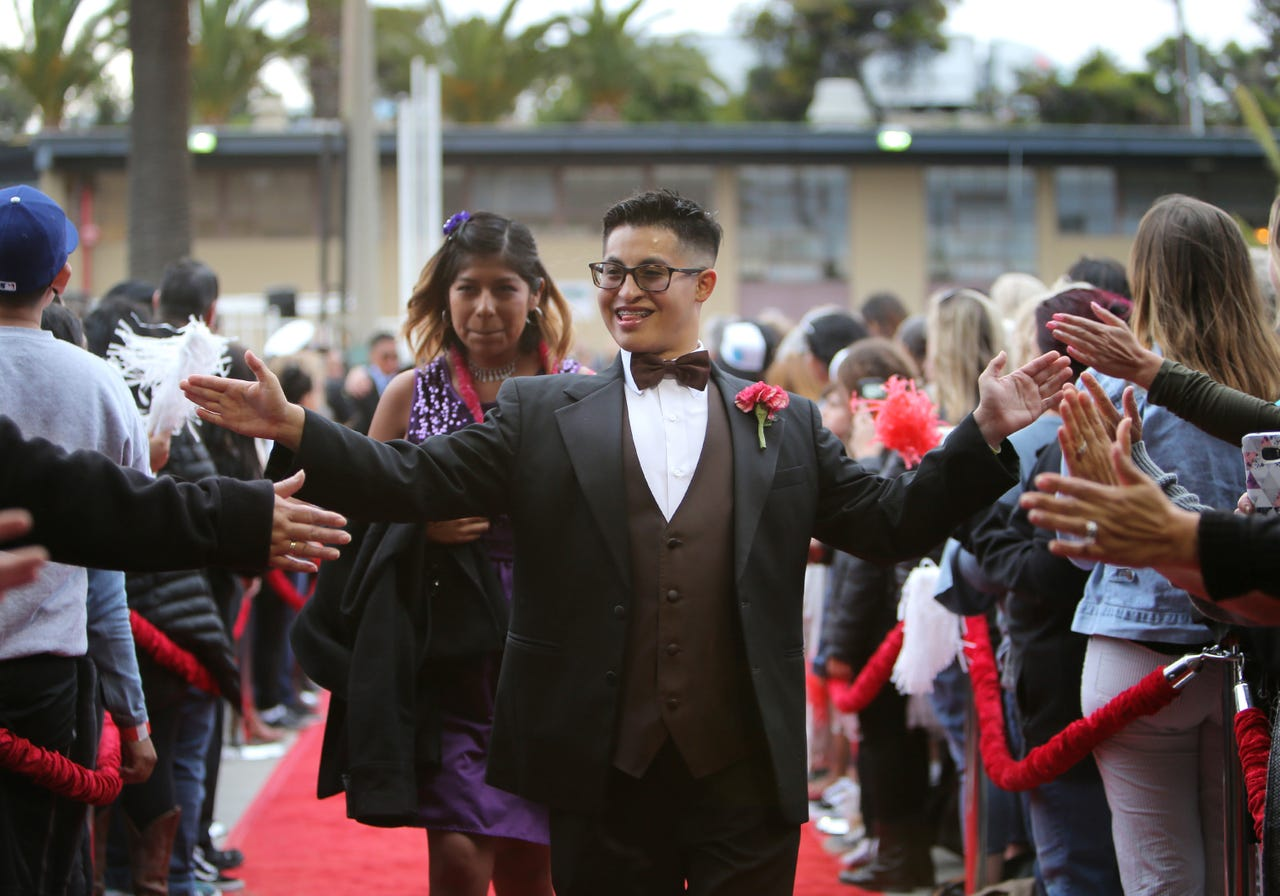 """Alec Cosio gives high-fives to guests as he and his student host Marilu Sanchez walk the red carpet during the eighth annual """"A Night to Remember"""" at the Ventura County Fairgrounds on Friday. The event, which is hosted by Mission Church in Ventura, is a free prom for students with disabilities from across Ventura County. More than 450 special needs students and more than 500 guests and 700 student hosts, with the help from more than 1,000 volunteers, made it a special night.  JOE LUMAYA/SPECIAL TO THE STAR"""