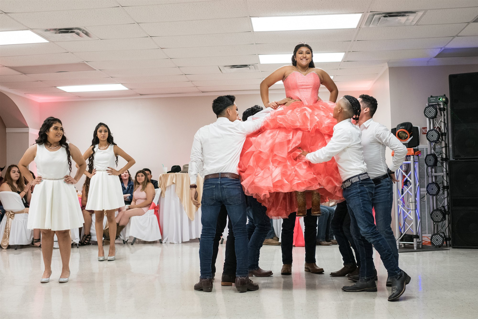 """Aleida Ramos is lifted in the air by the chamberlains of her court of honor while celebrating her quinceañera with family and friends in Houston. During a short speech, Ramos encouraged those eligible to register to vote at a """"Poder Quince"""" station set up near the event hall's front door.Loren Elliott / for NBC News"""