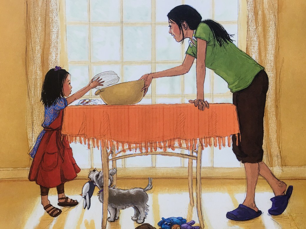 [Image description: Illustration from 'Cora Cooks Pancit' by Dorina  K. Lazo Gilmore and Kristi Valiant. A Filipina mother holds a large bowl  steady while her daughter puts in noodles.]